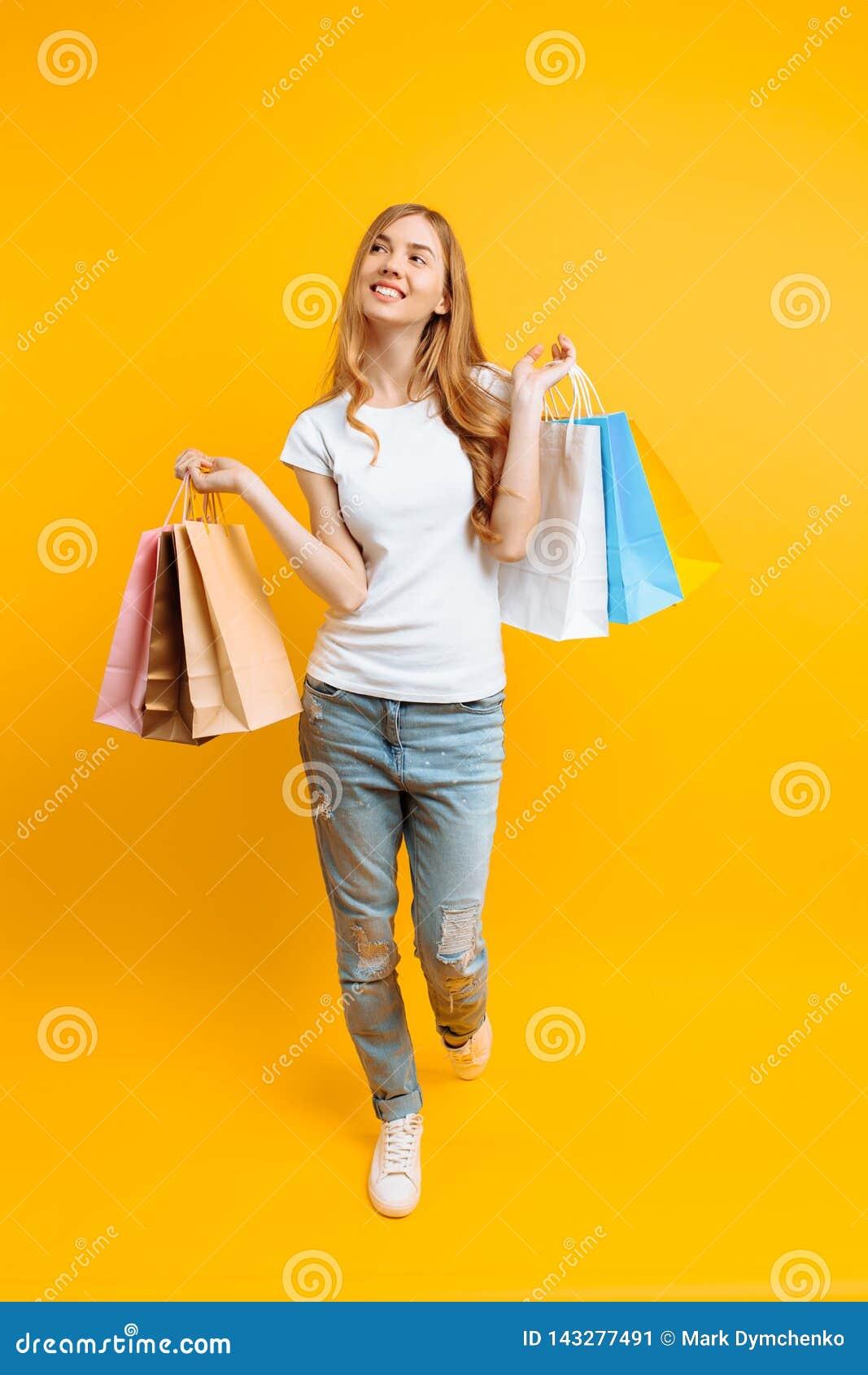 Retrato integral de una mujer hermosa joven, con los bolsos multicolores, en un fondo amarillo