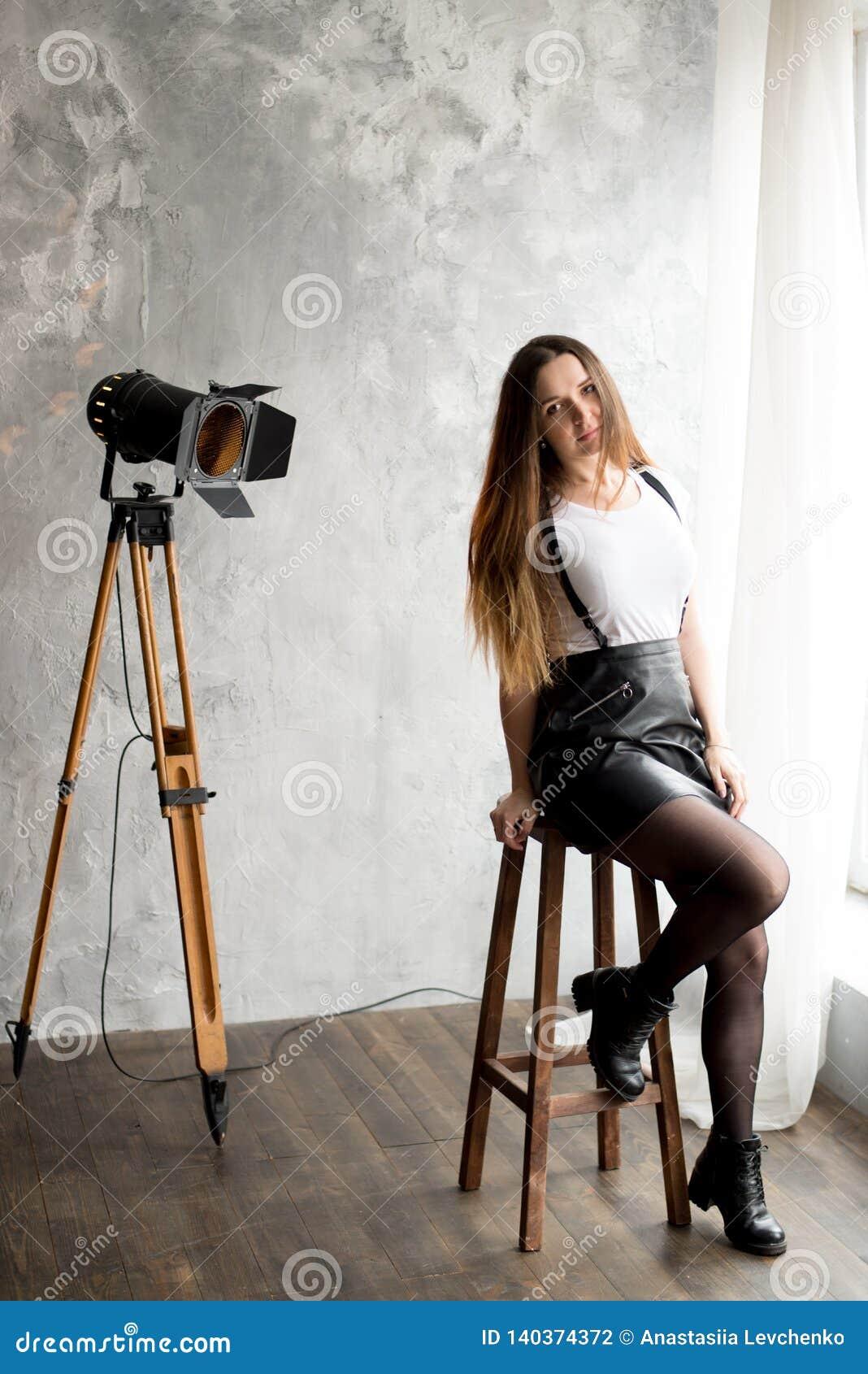 Retrato integral de una mujer joven sonriente que se sienta en silla