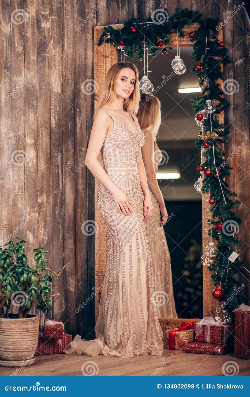 Retrato integral de una mujer rubia elegante atractiva en un vestido de oro largo cerca del espejo adornado con las ramas de la N