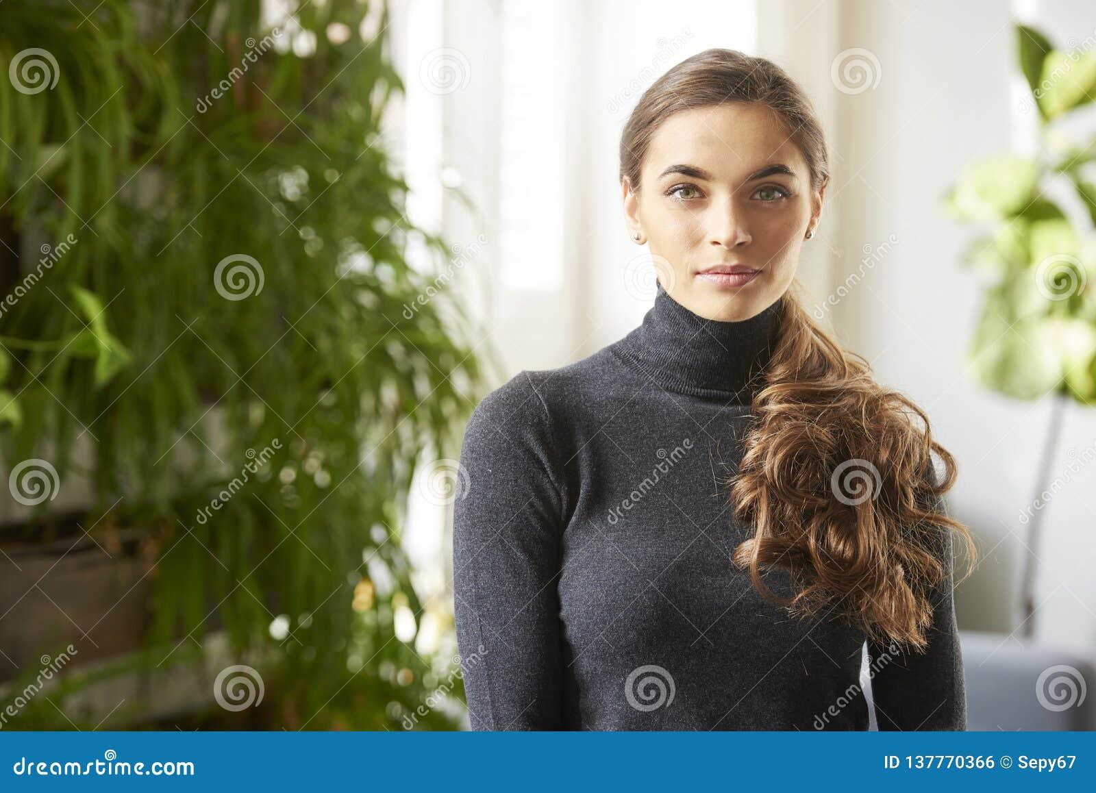 Retrato interior atractivo de la mujer joven