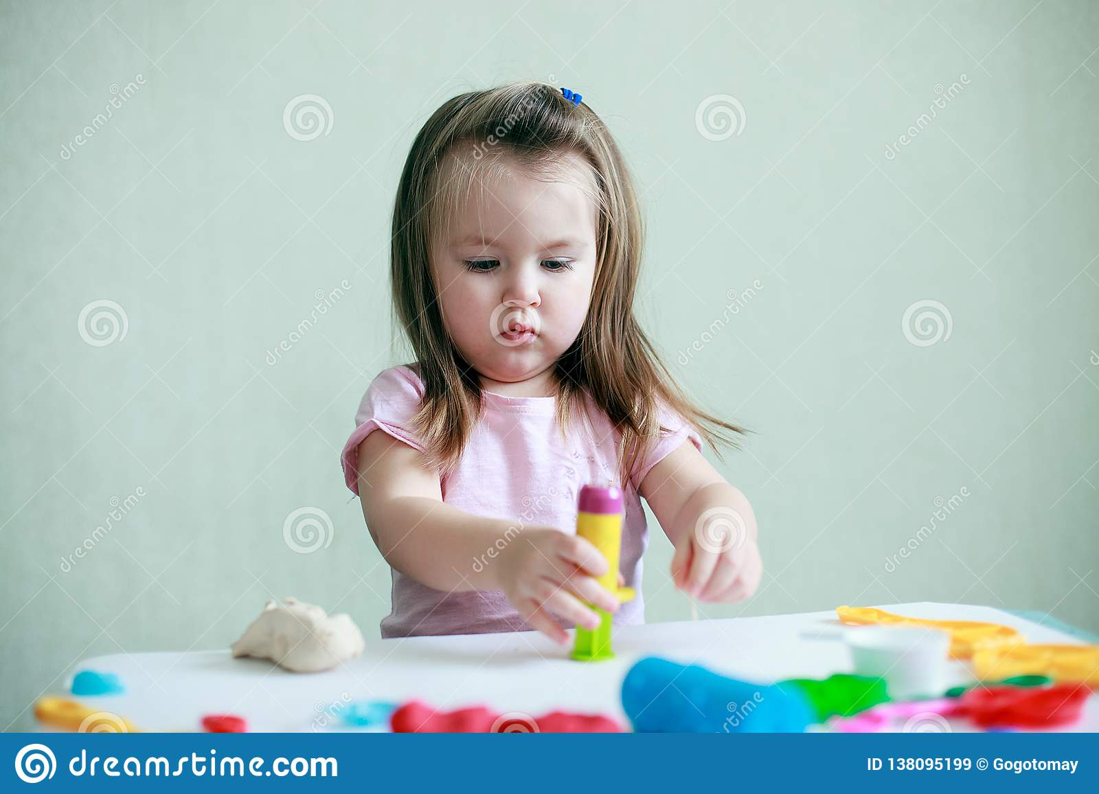 Retrato interior de los 2 años jovenes de muchacha caucásica sonriente feliz del niño que juega con pasta del juego