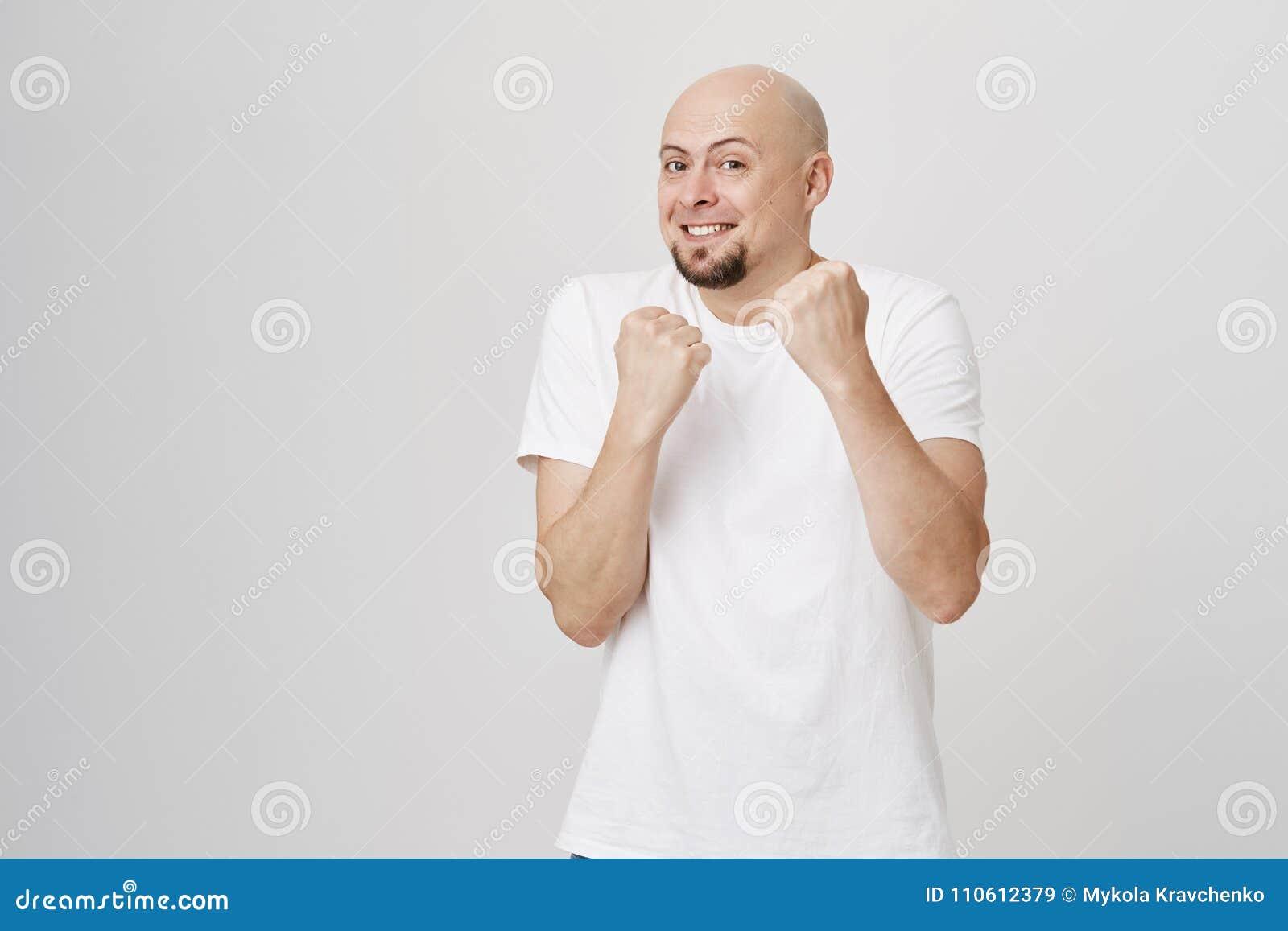 Retrato interior del hombre barbudo caucásico calvo juguetón encantador que se coloca en la actitud del boxeador que defiende, fa