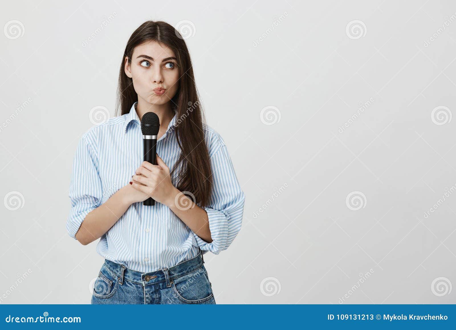 Retrato interno da jovem mulher perplexo e questionada, guardando o microfone ao pensar e ao olhar de lado, estando
