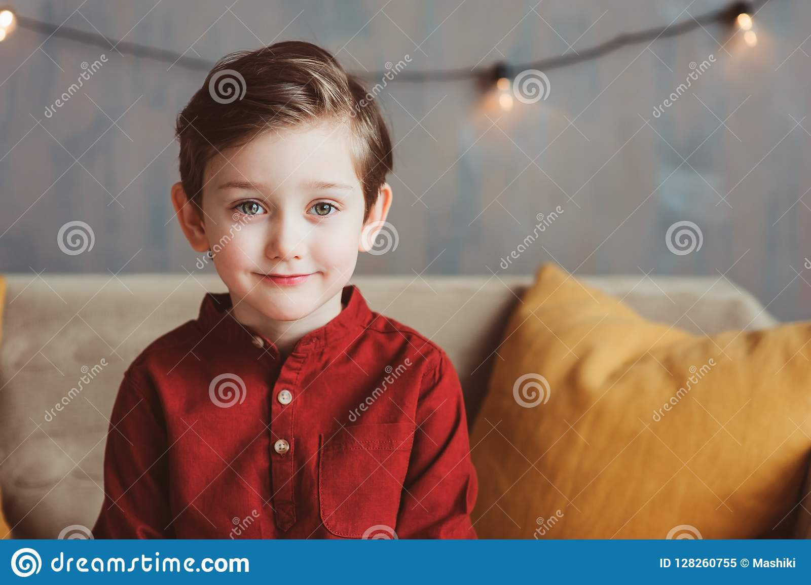 Retrato interno do menino à moda considerável feliz da criança que senta-se no sofá acolhedor
