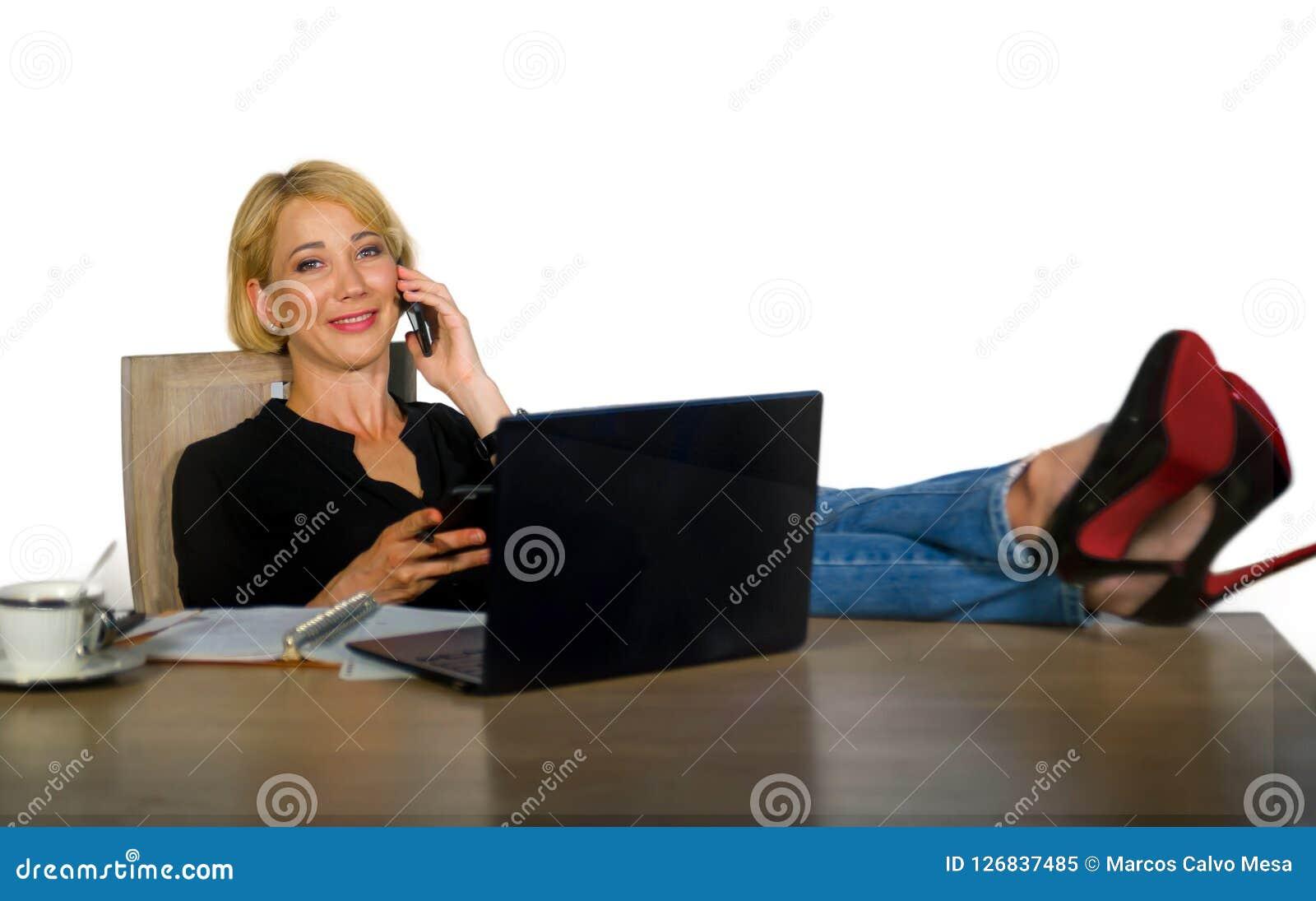 Retrato isolado da empresa da mulher bonita e feliz nova com cabelo louro que sorri ao trabalhar relaxado no escritório l