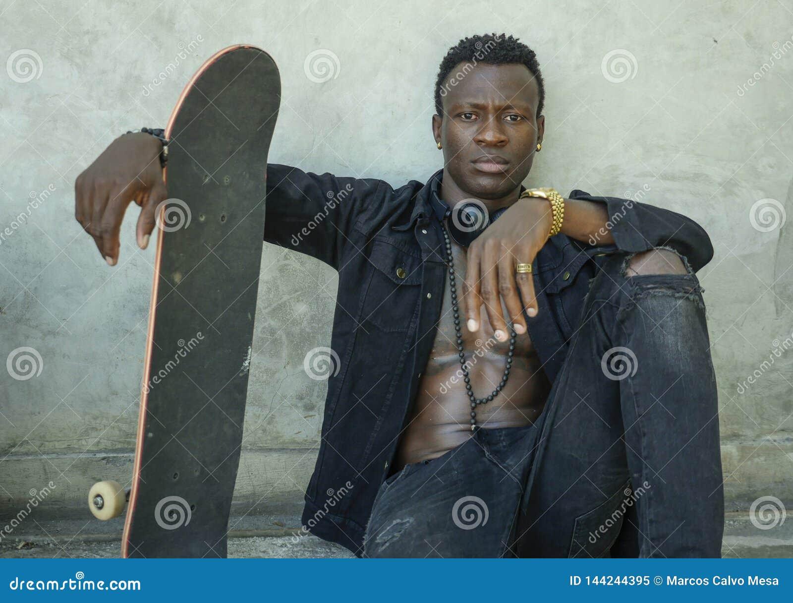 Retrato isolado fresco do homem afro-americano preto novo do moderno atrativo e seguro que inclina-se no patim da terra arrendada