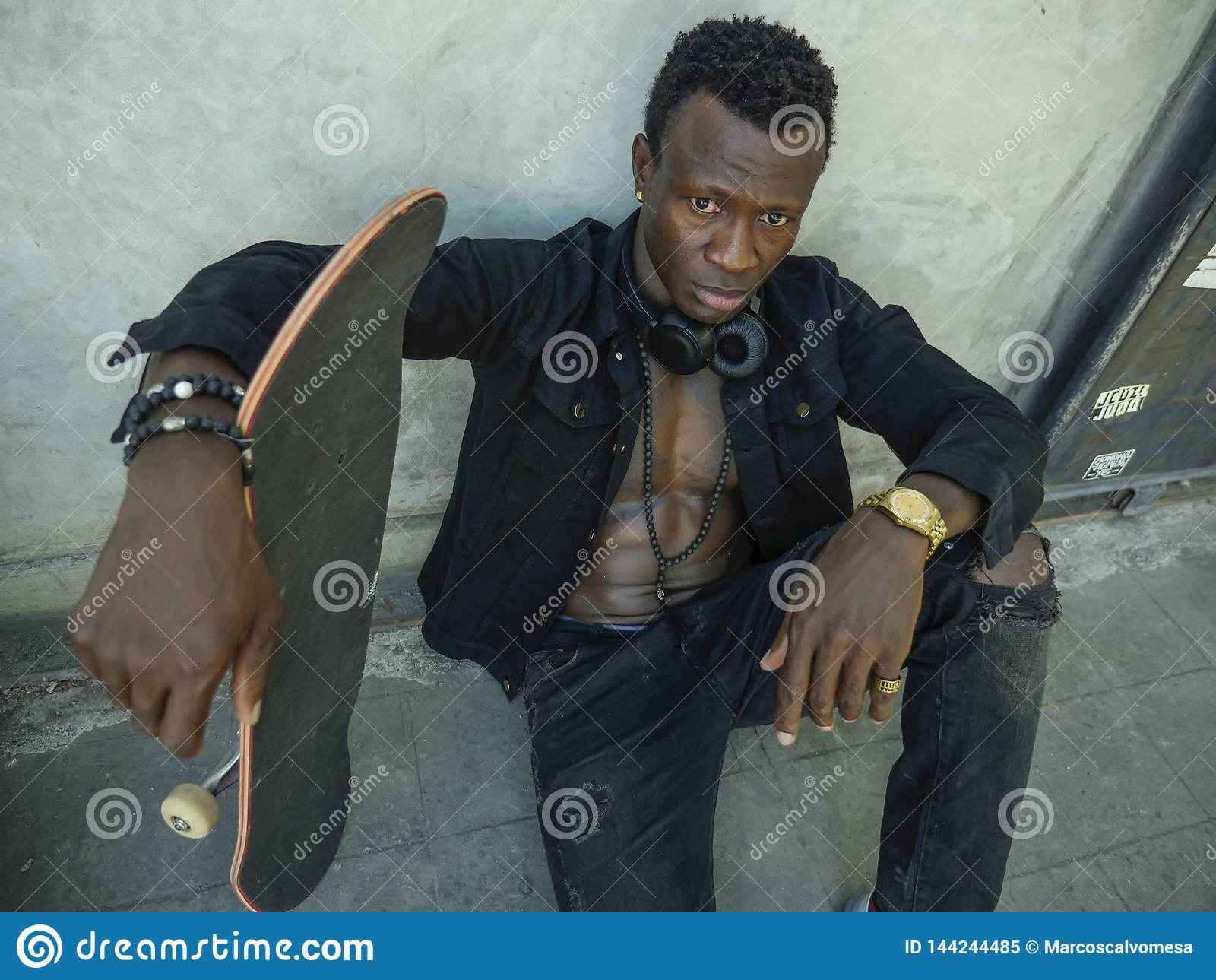 Retrato isolado fresco do homem americano novo do africano negro atrativo e seguro do moderno que inclina-se no patim da terra ar