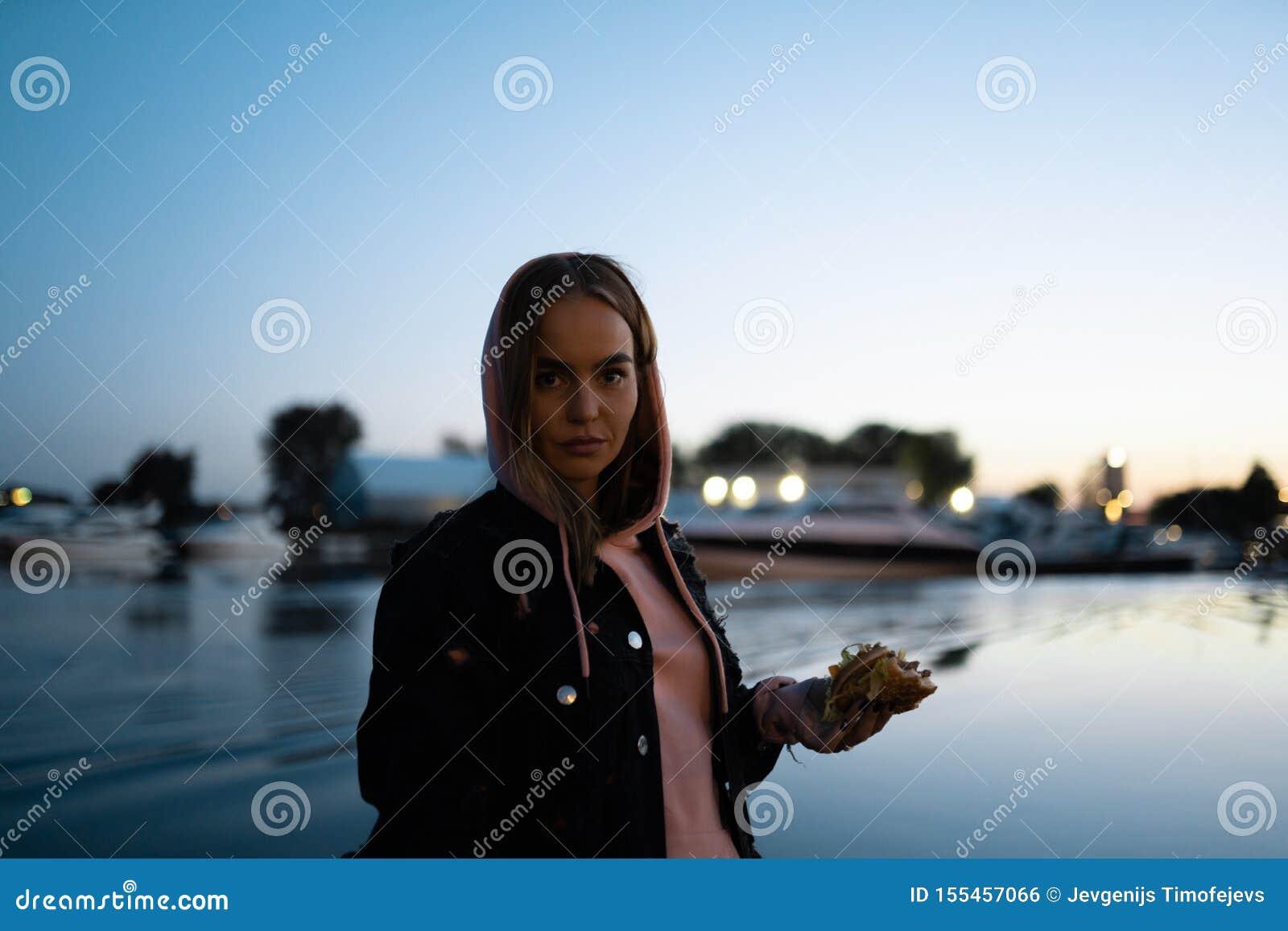 Retrato louro da mulher que come os vidros vestindo do hamburguer que estão pelo rio na noite