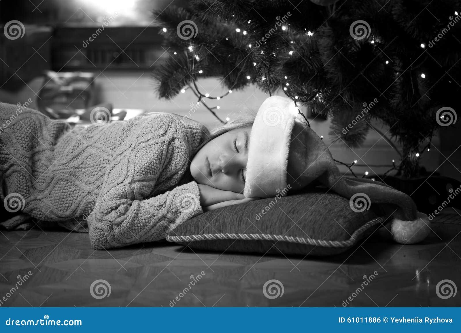 Retrato monocromático da menina bonito que dorme sob a árvore de Natal