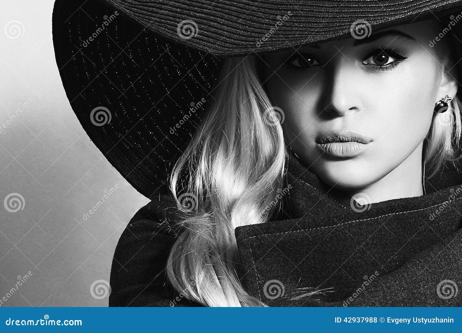Retrato monocromático da mulher loura bonita no chapéu negro Senhora elegante no sobretudo