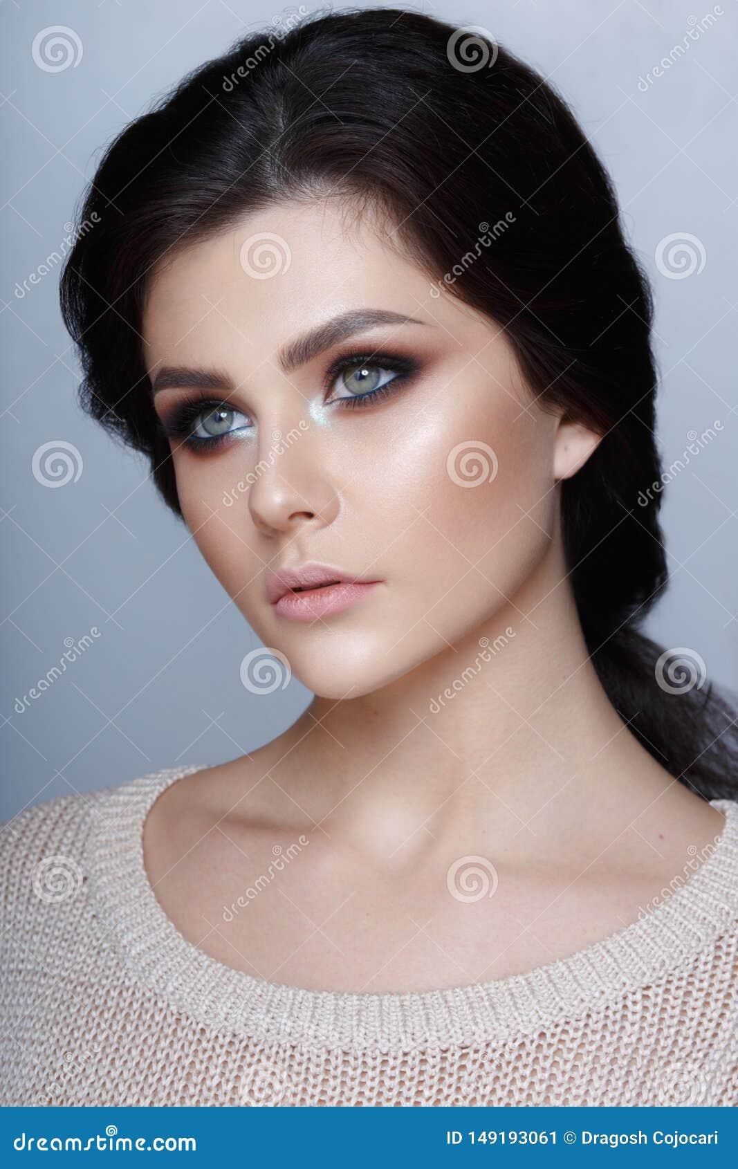 Retrato natural del perfil de la belleza de una muchacha morena joven con la piel natural en fondo gris Tiro vertical del estudio