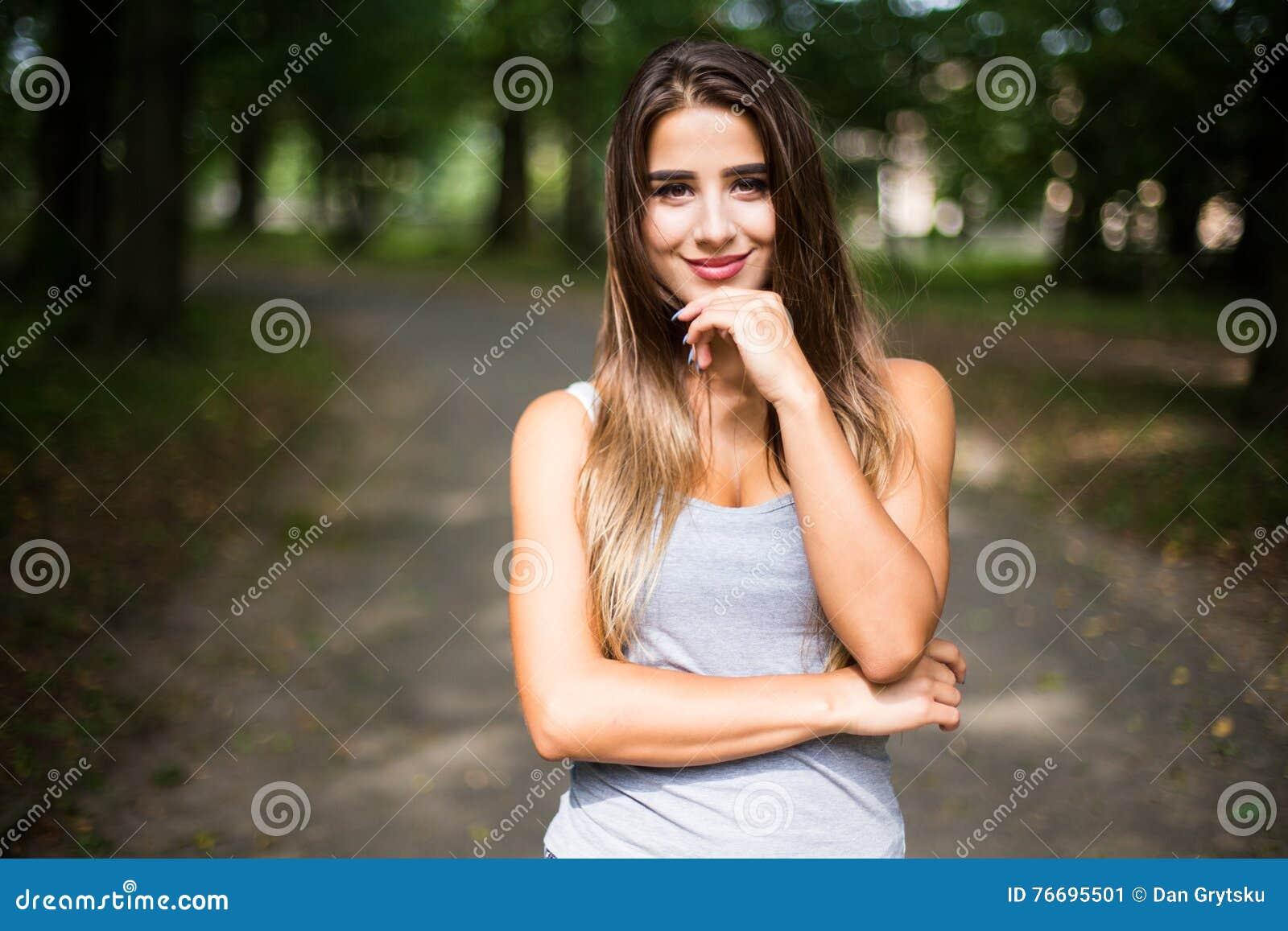 Retrato no parque de uma menina adolescente bronzeada bonita do estudante