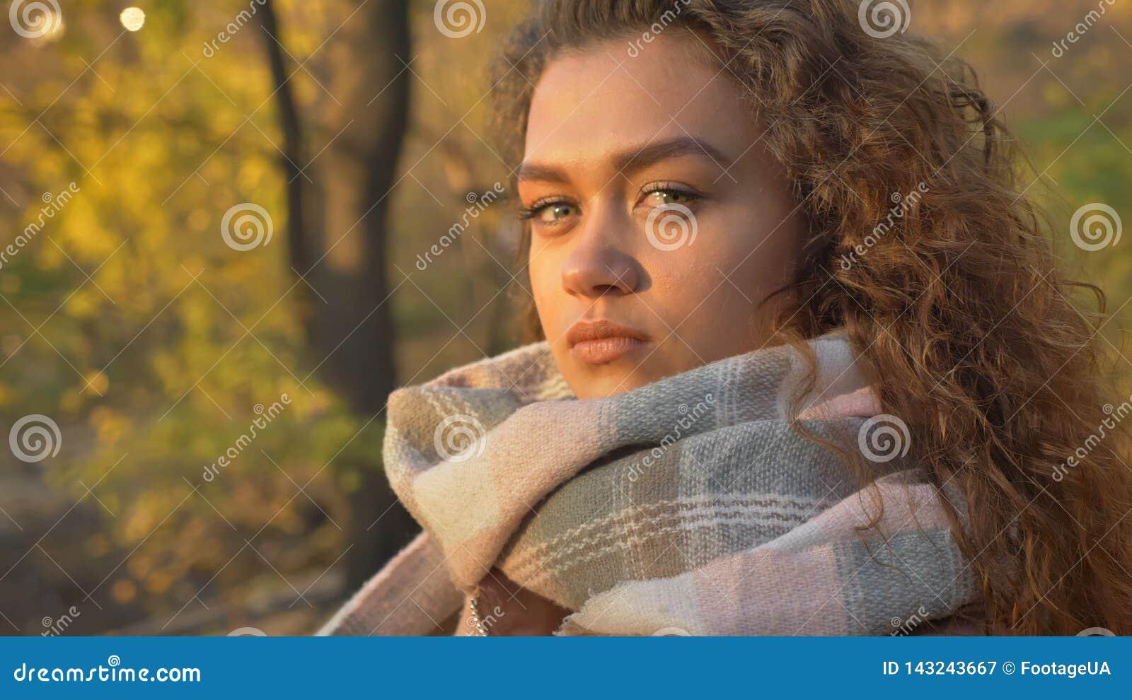 Retrato no perfil da menina caucasiano consideravelmente encaracolado-de cabelo que olha seriamente na câmera no parque outonal