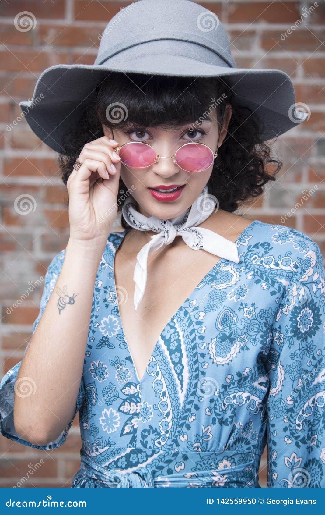 Retrato oriental bonito da mulher com vidros coloridos cor-de-rosa e o chapéu elegante do sol com tatuagem pequena, vestido bonit