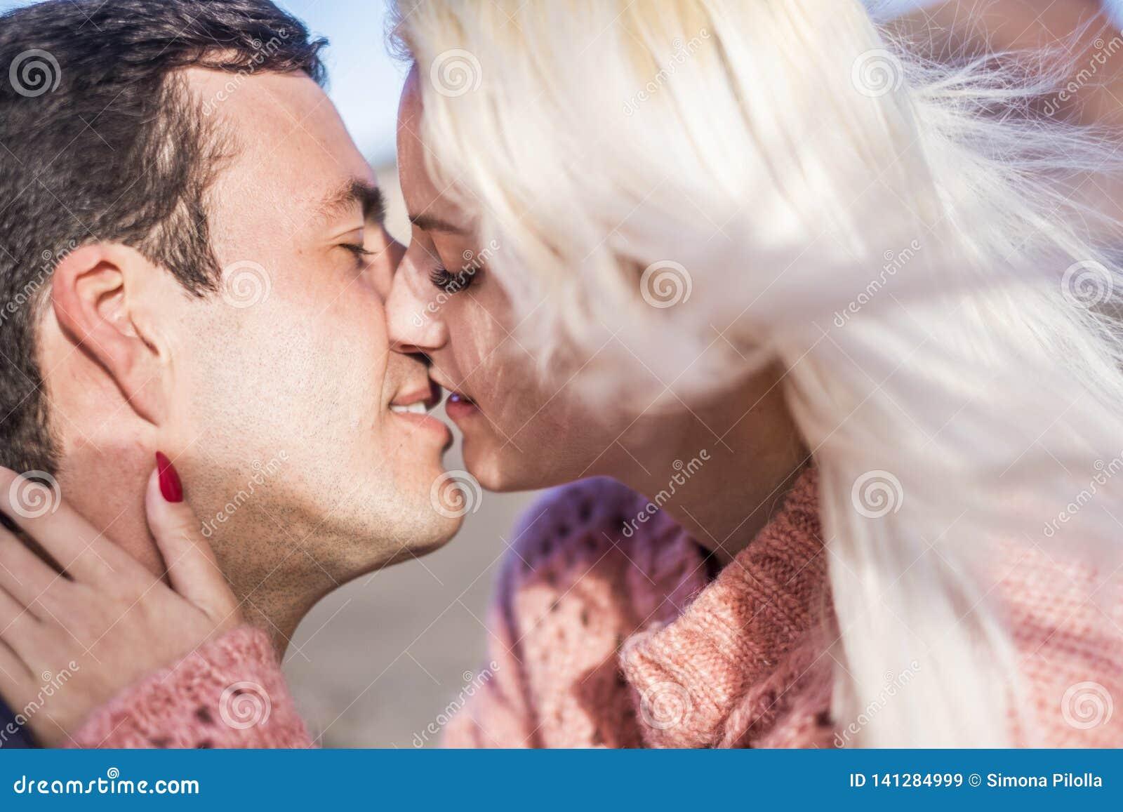 Retrato próximo dos pares caucasianos bonitos que beijam-se close up apaixonado com beijo Homem novo e mulher Conceito do amor