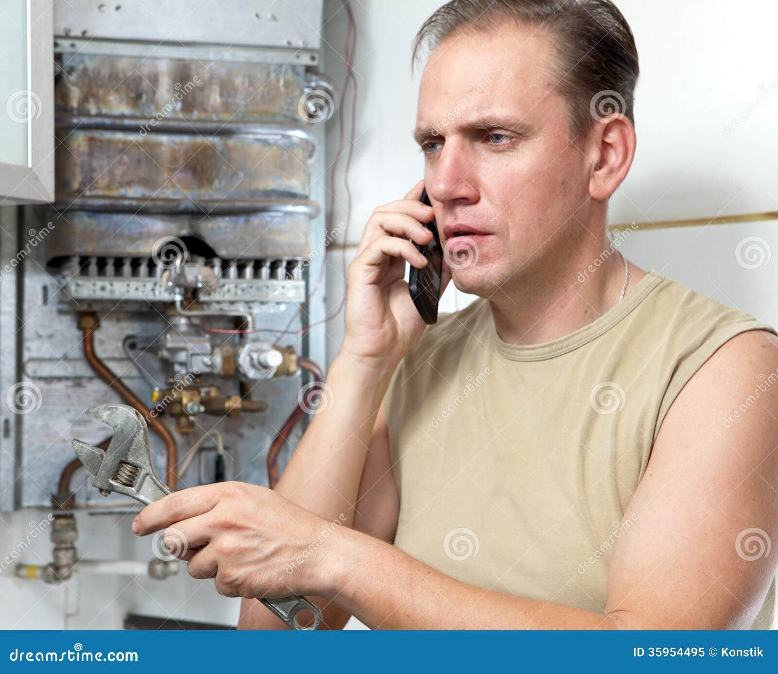 Retrato que el hombre llama por el teléfono para causar al reparador de los calentadores de agua del gas