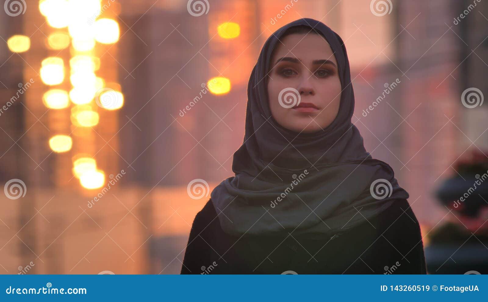 Retrato recto del primer de la hembra bonita joven en el hijab que mira adelante la cámara con la ciudad urbana y que brilla