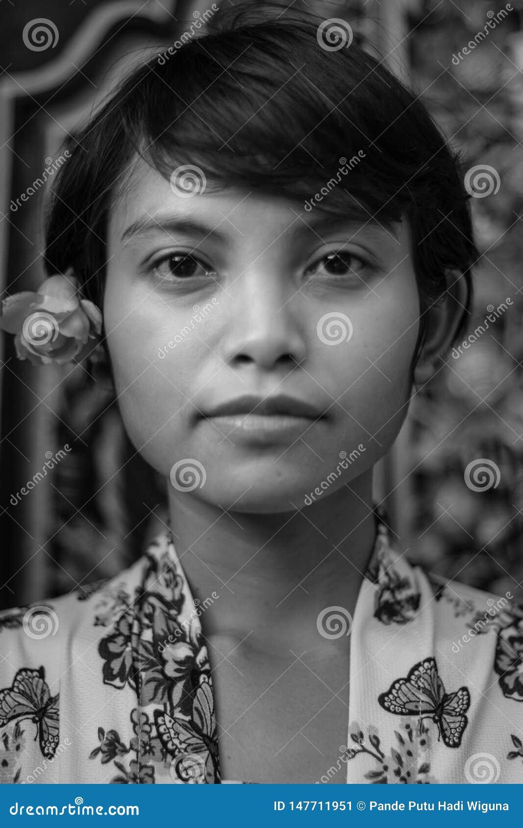 Retrato retro monocrom?tico blanco y negro de una mujer asi?tica hermosa del Balinese del pelo corto que lleva estilo floral del