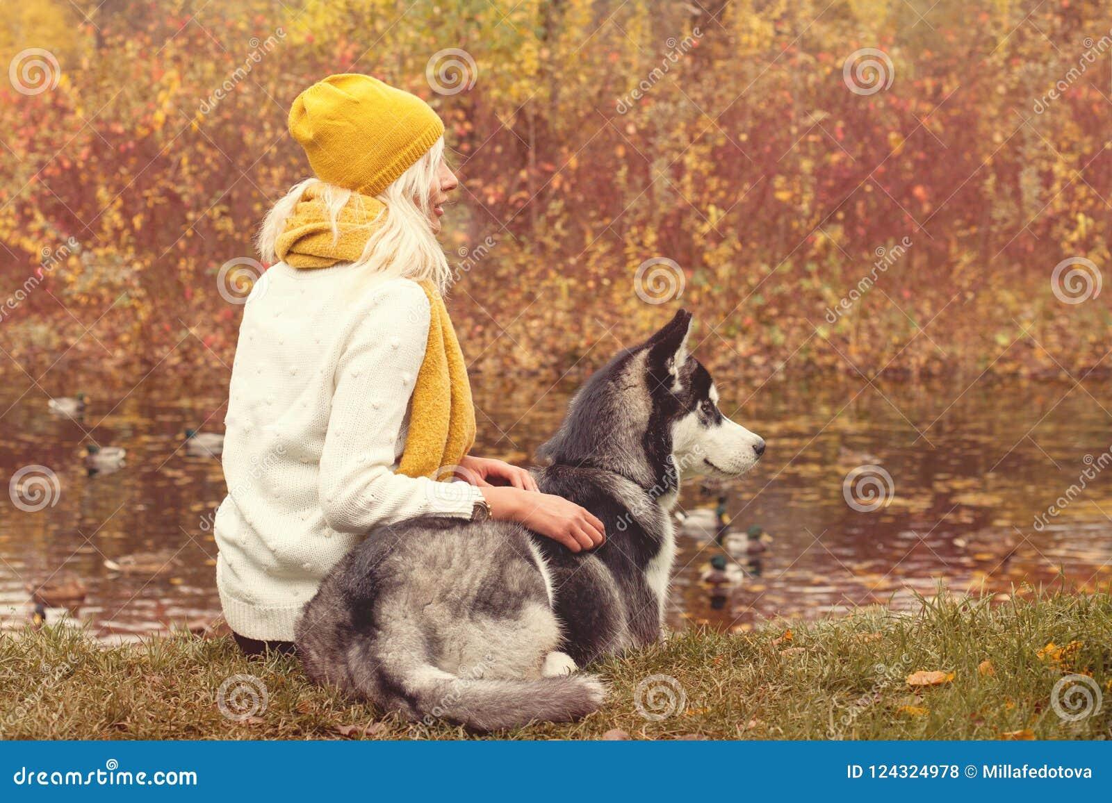Retrato romántico del otoño de una mujer y de su perro