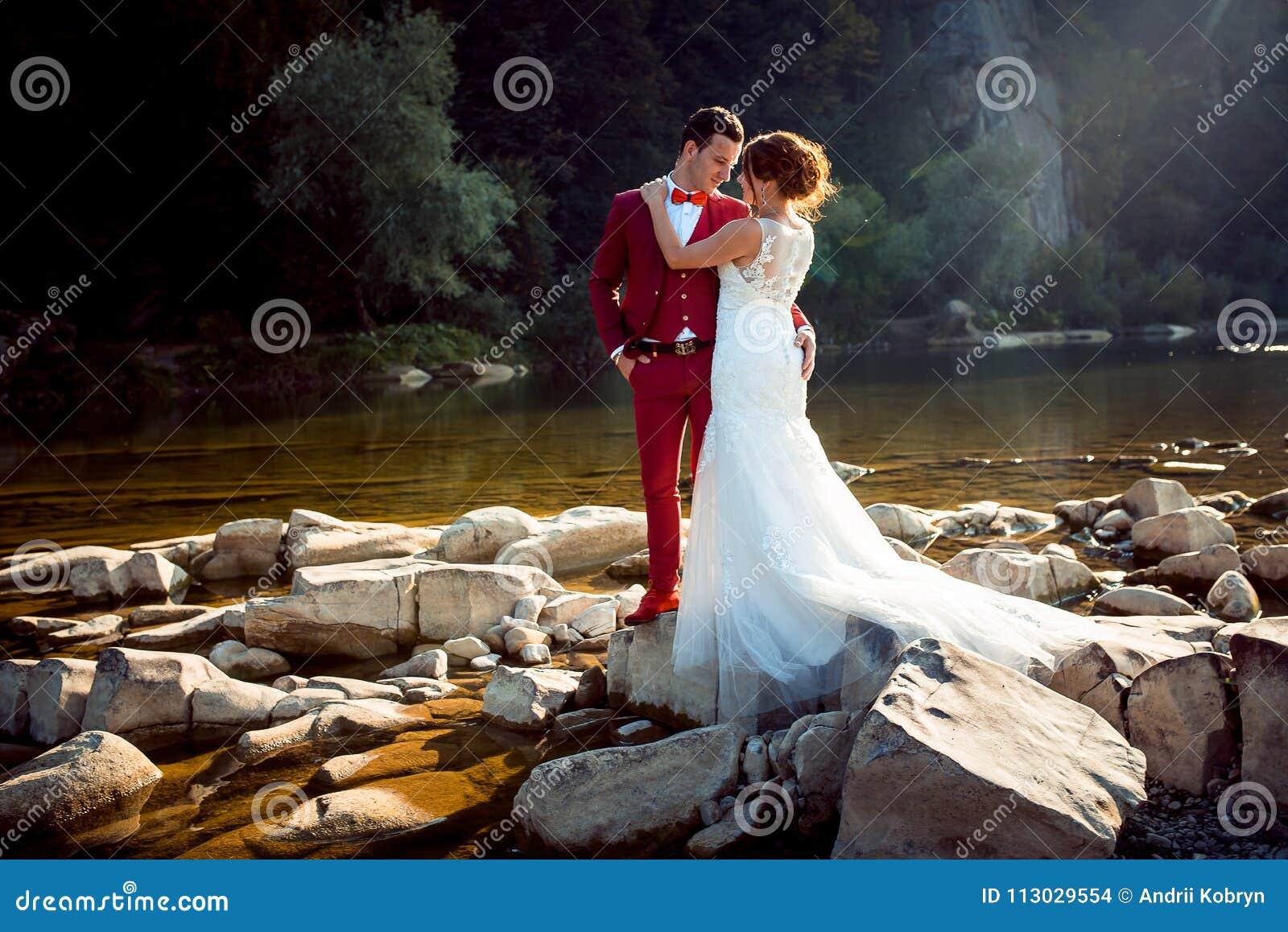 Retrato sensible de los pares de la boda que abrazan en los riverstones durante la puesta del sol Tiro horizontal