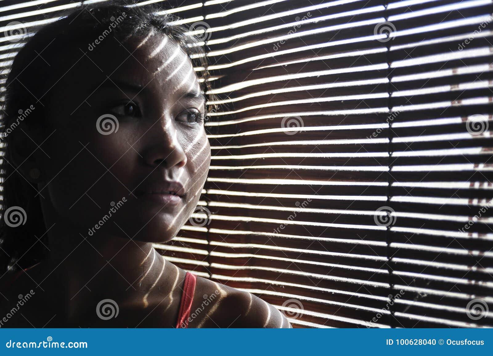 Retrato sombrío de la mujer asiática hermosa joven en los paños del deporte del gimnasio que miran a través de las persianas