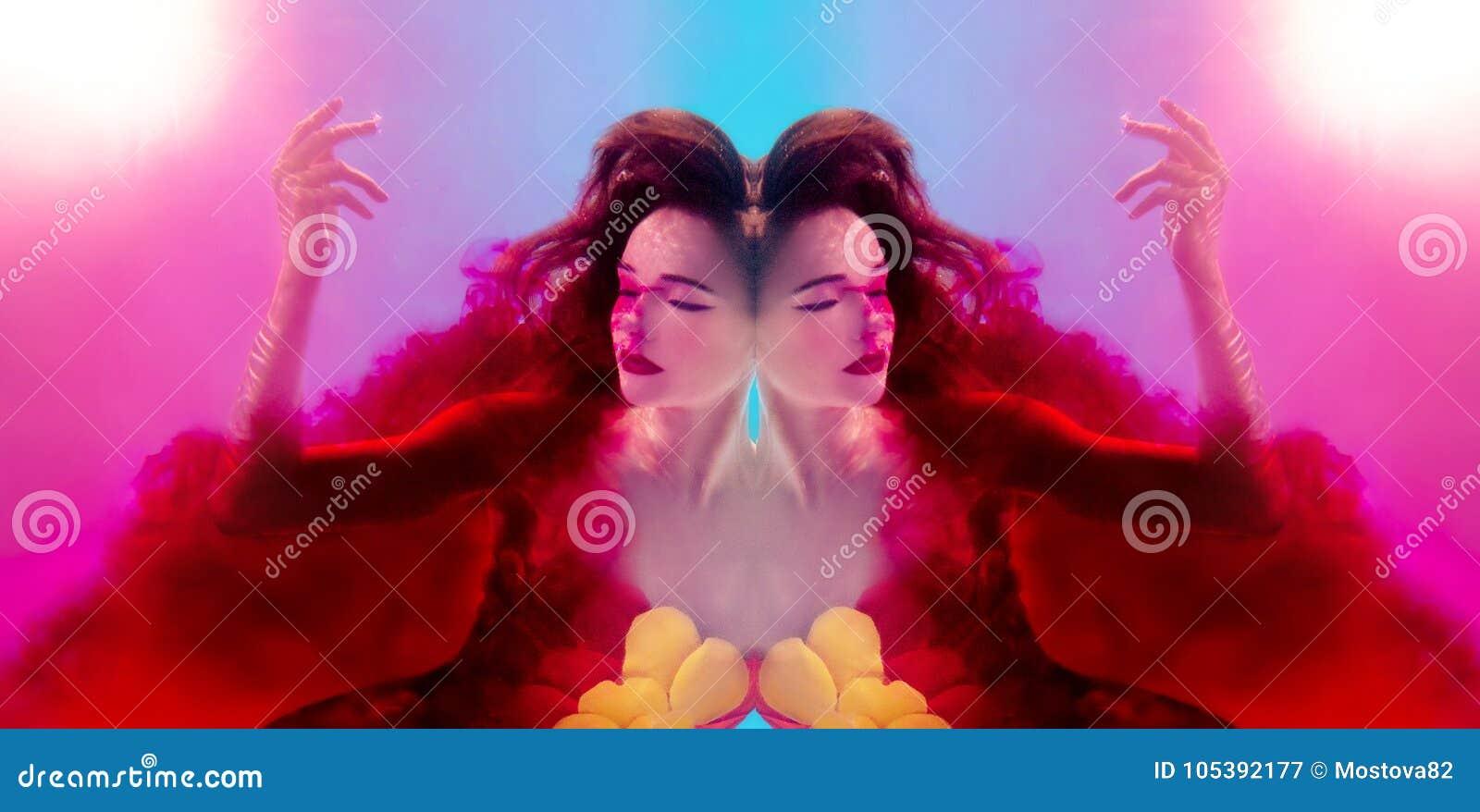 Retrato surrealista de la mujer atractiva joven con las burbujas de aire subacuáticas en agua colorida con tinta