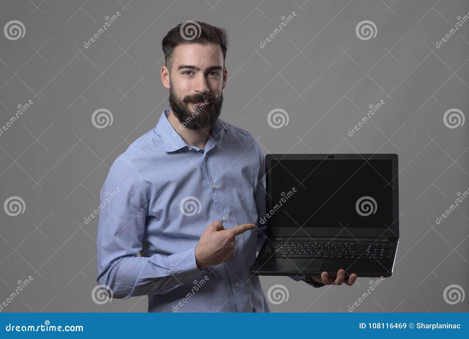 Retrato temperamental do homem de negócio adulto novo feliz de sorriso que guarda o portátil e apontar e tela de computador vazio
