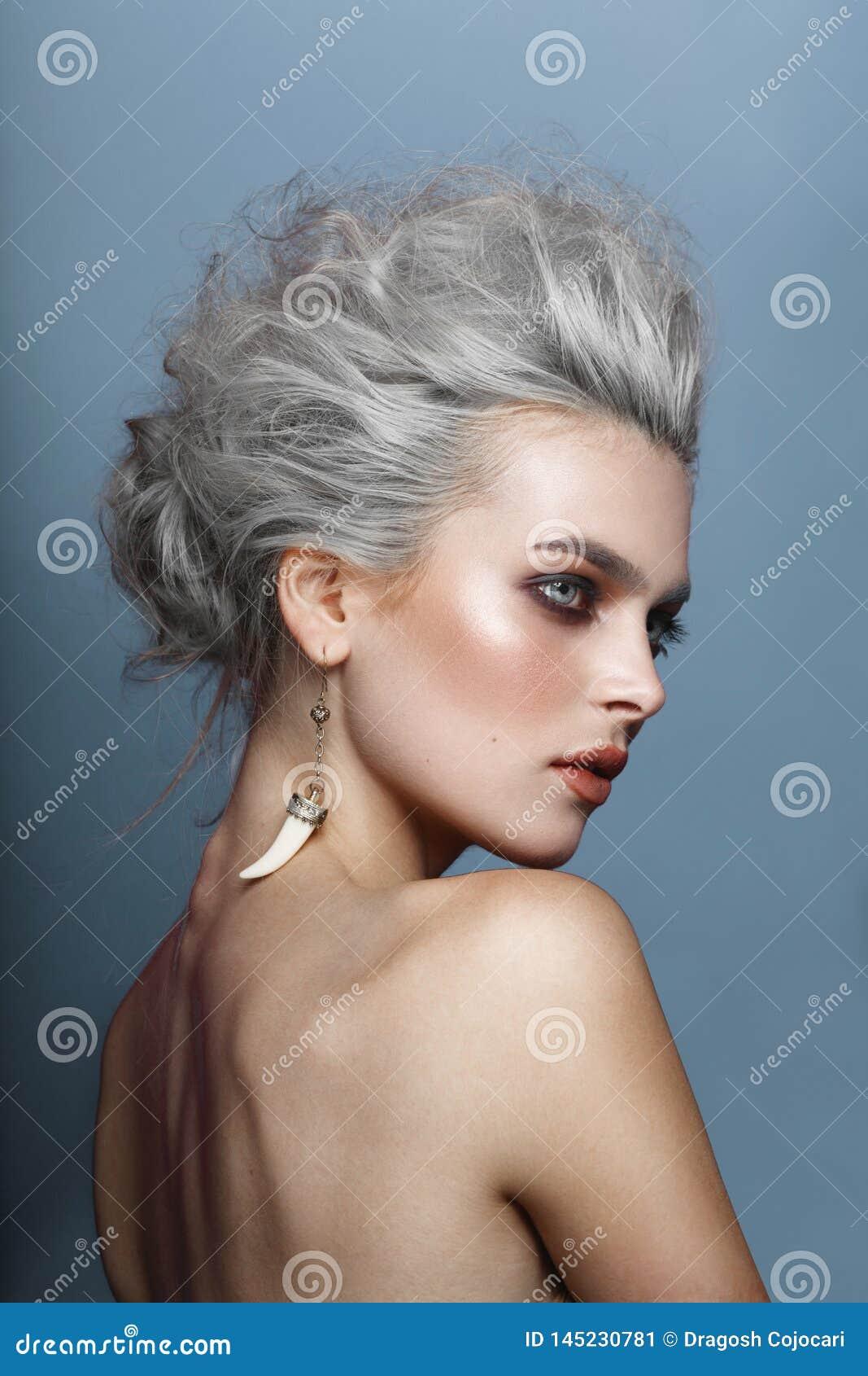 Retrato trasero de una mujer joven con los hombros desnudos, teniendo un pelo que diseña, maquillaje, en un fondo azul