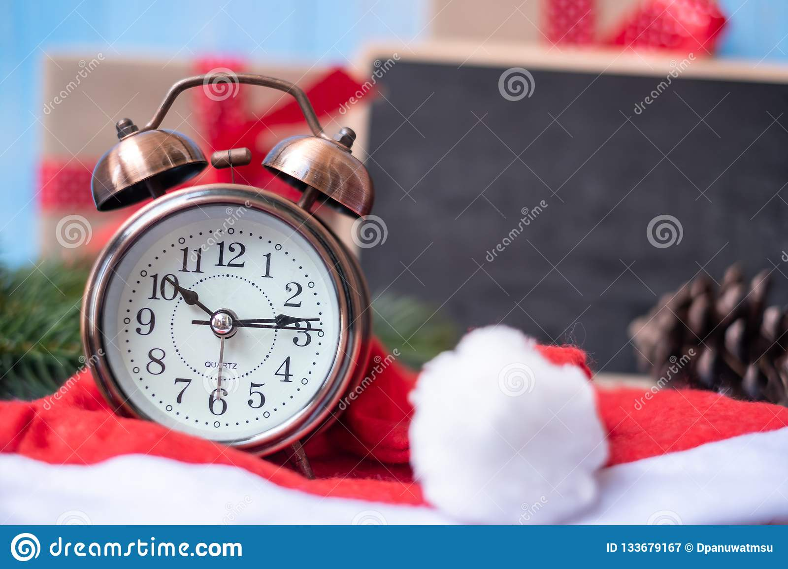 Retro alarm clock with Merry Christmas gift box or Present and Santa Claus hat on blue wooden background
