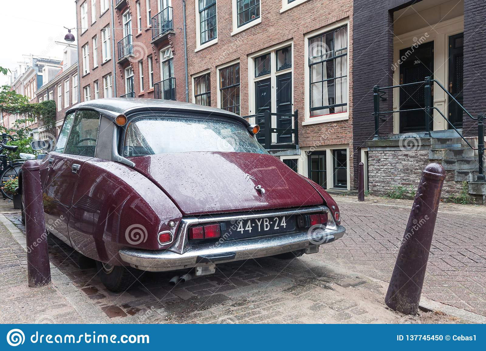 Retro automobile d annata di Citroen da dietro parcheggiato sulla via di Amsterdam il giorno piovoso
