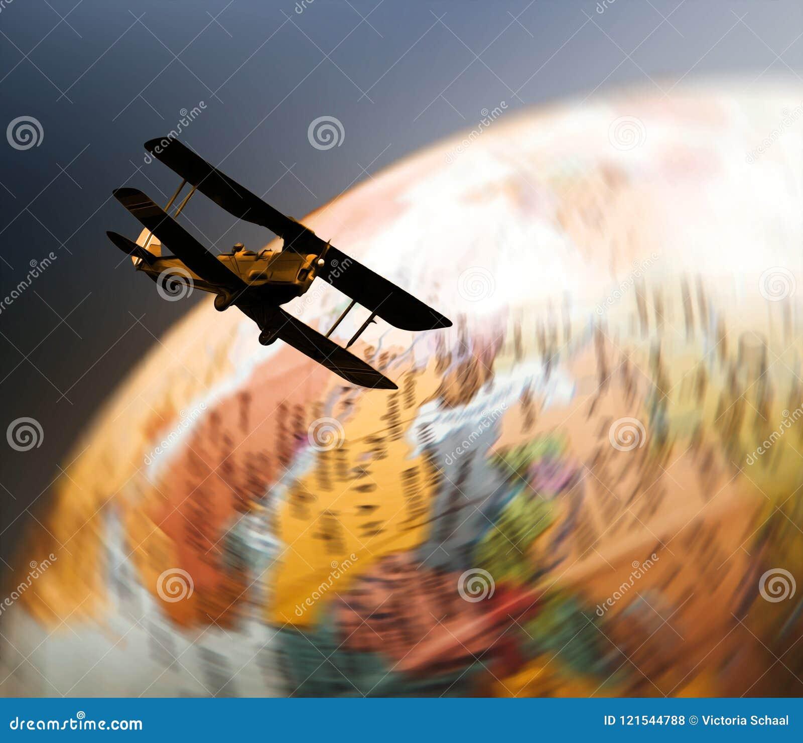 Retro biplane flying over spinning globe