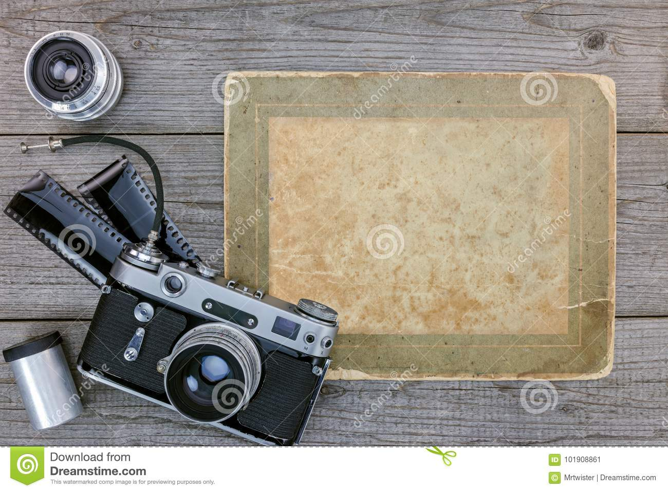 Retro camera, negative film, lenses on wooden table background