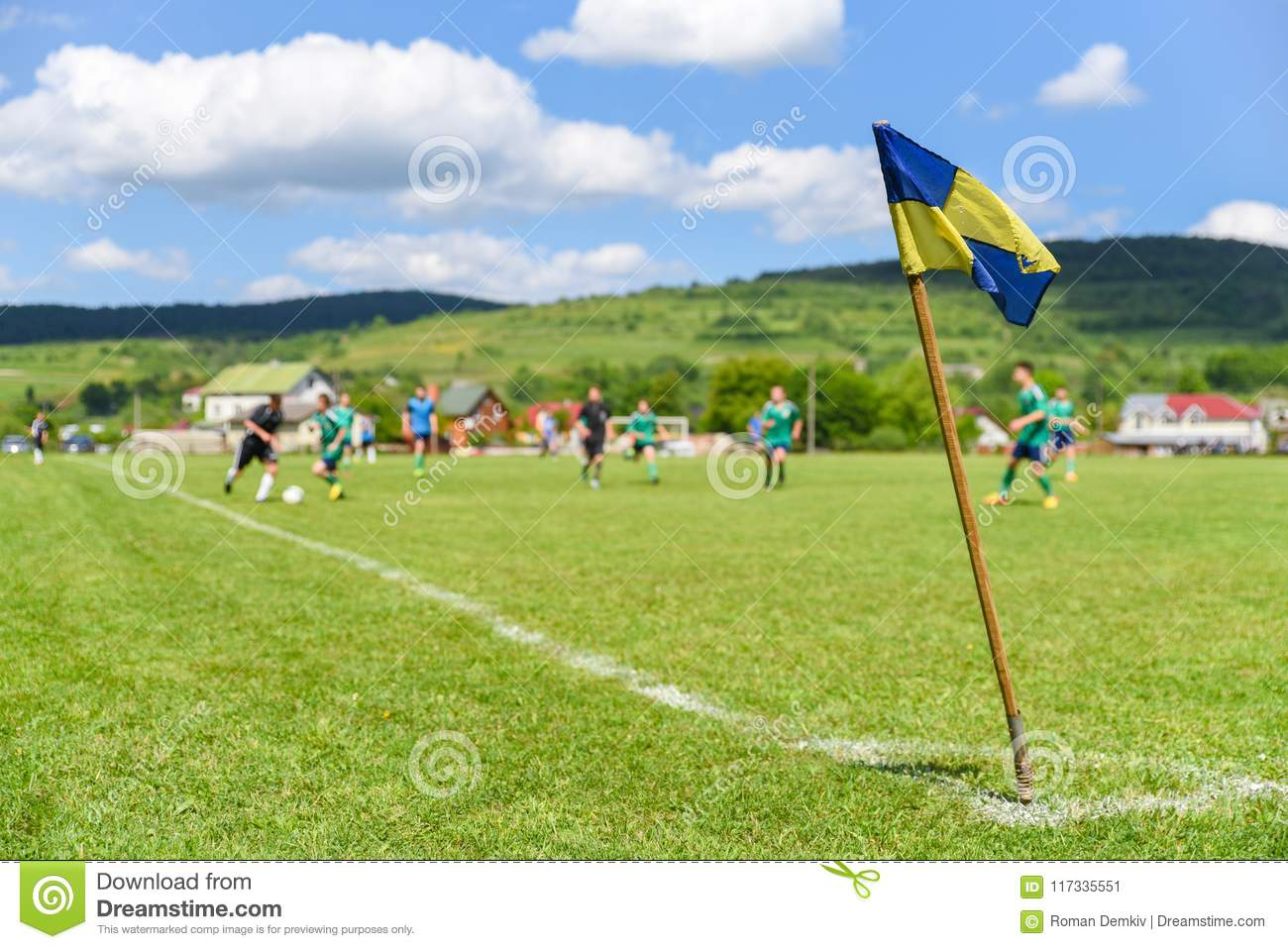 Retro corner flag on the foreground of amateur soccer field, on blurry background are football players fighting for the ball