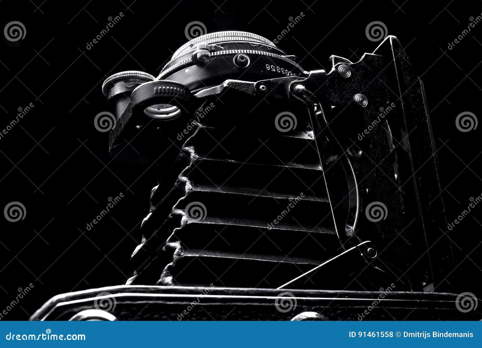 Retro dichte omhooggaand van de fotocamera op de zwarte achtergrond