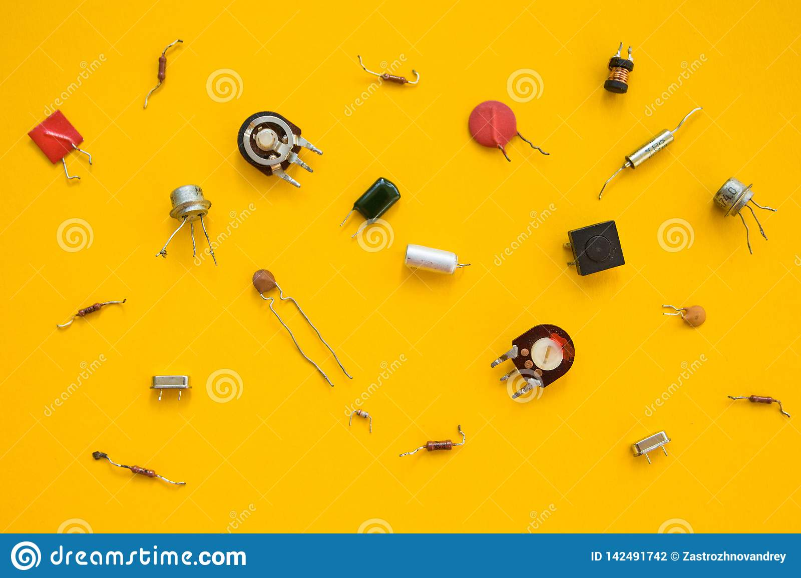 Retro electronic components  in yellow background, concept. The flat composition