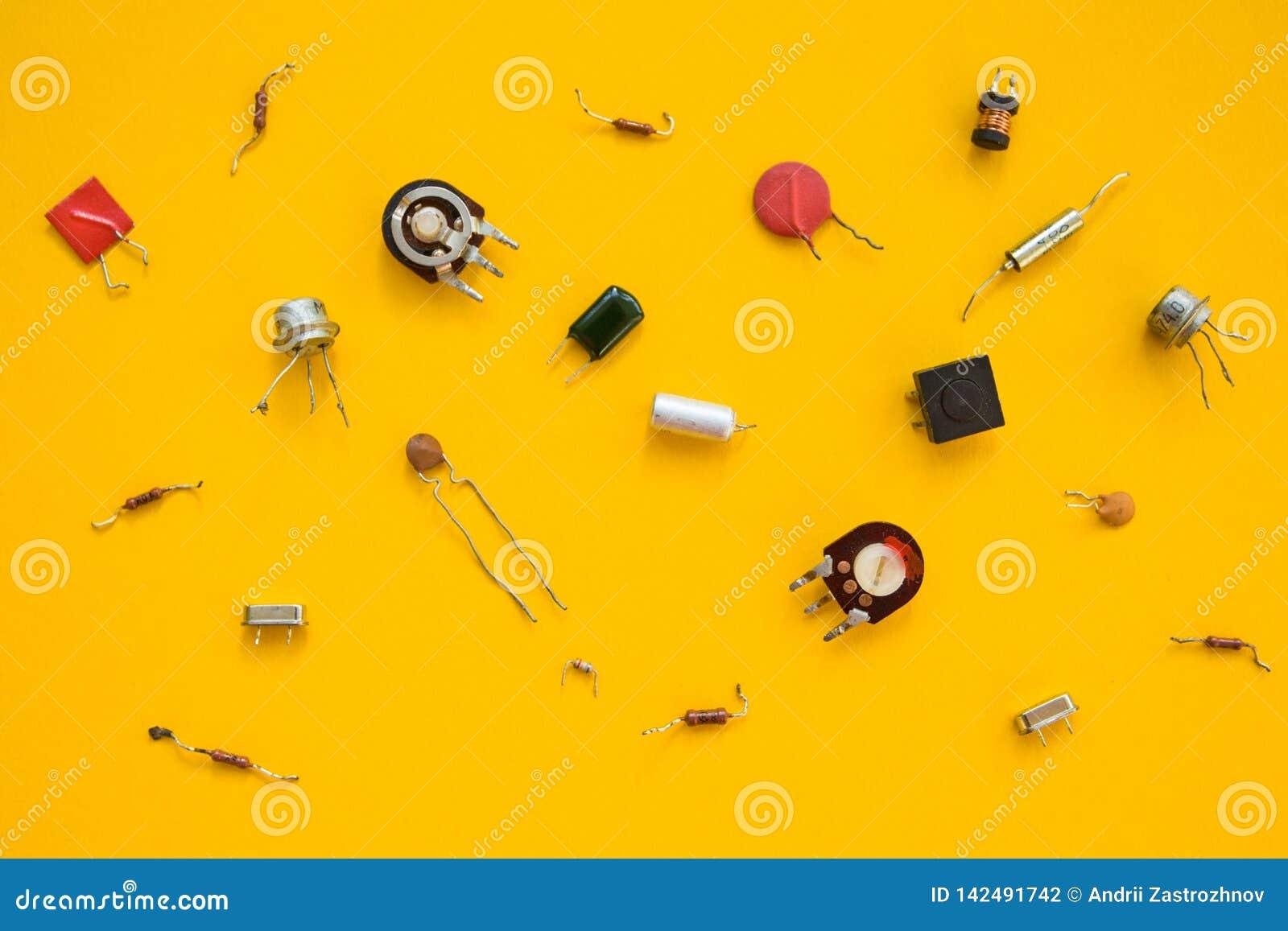 Retro elektroniska delar i gul bakgrund, begrepp Den plana sammansättningen