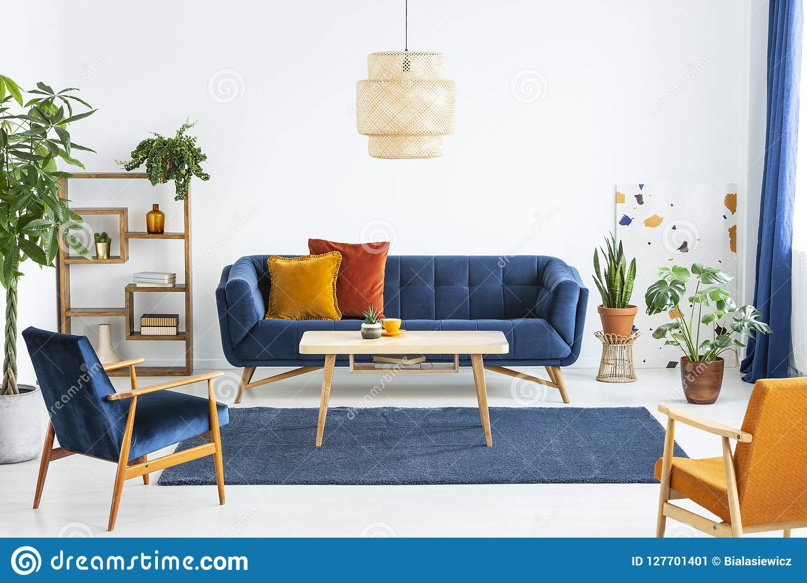 Retro fåtöljer med träramen och färgrika kuddar på en marinblå soffa i en vibrerande vardagsruminre med gröna växter Beträffande