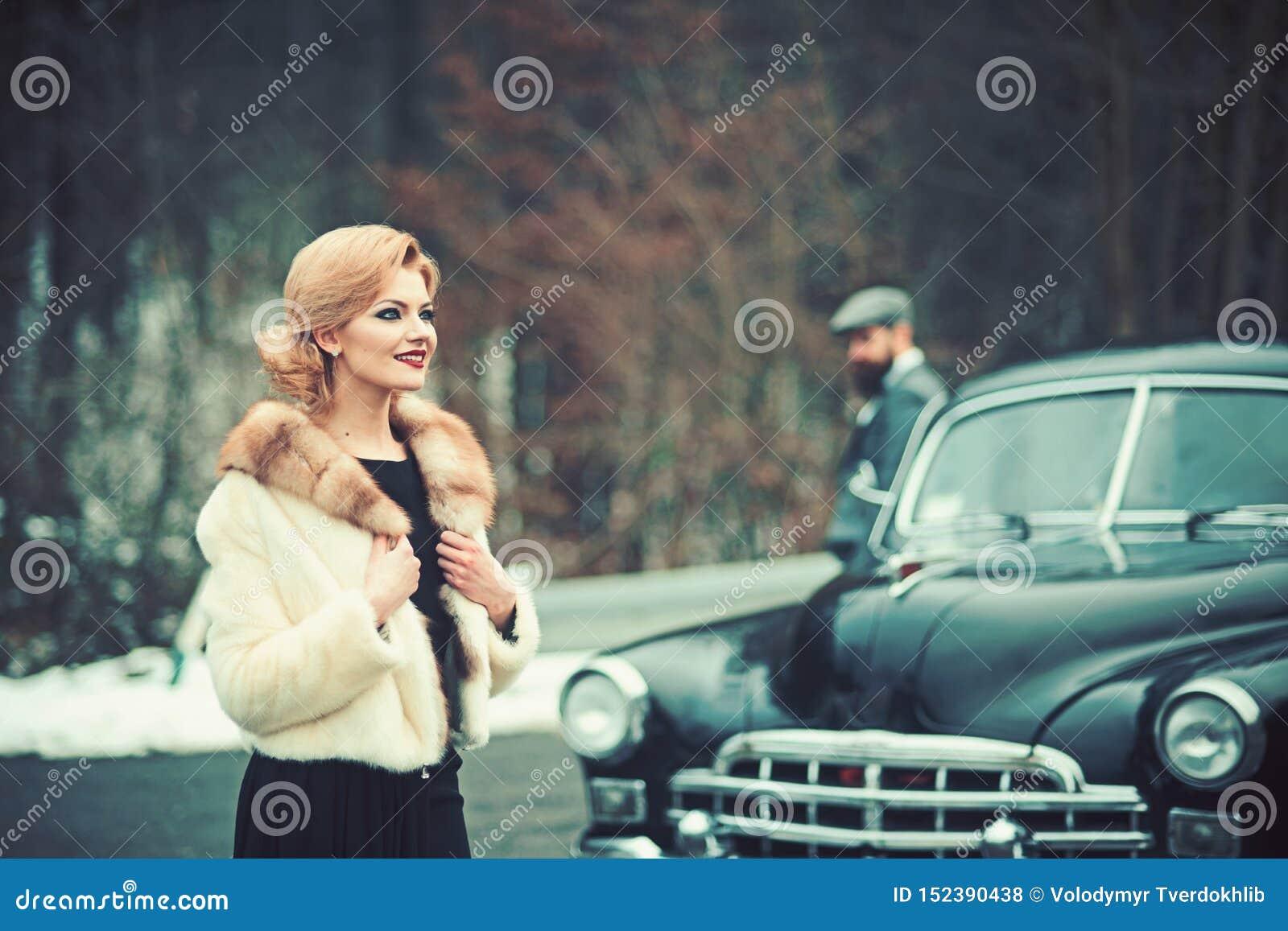 Retro- Foto der Frau und des Mannes mit zwei Reisenden im Retro- Auto