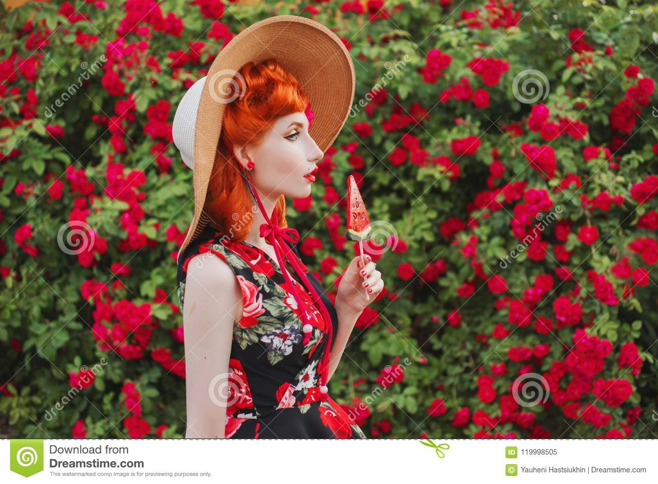 Retro girl with red lips in a dress with a print of roses with red candy on  summer background. Young redhead model in a hat on a background of a bush  of ...