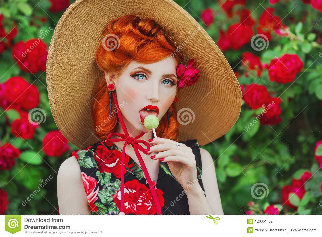 Retro girl with red lips in a dress with a print of roses with yellow lollipop on summer background. Young redhead model in a hat