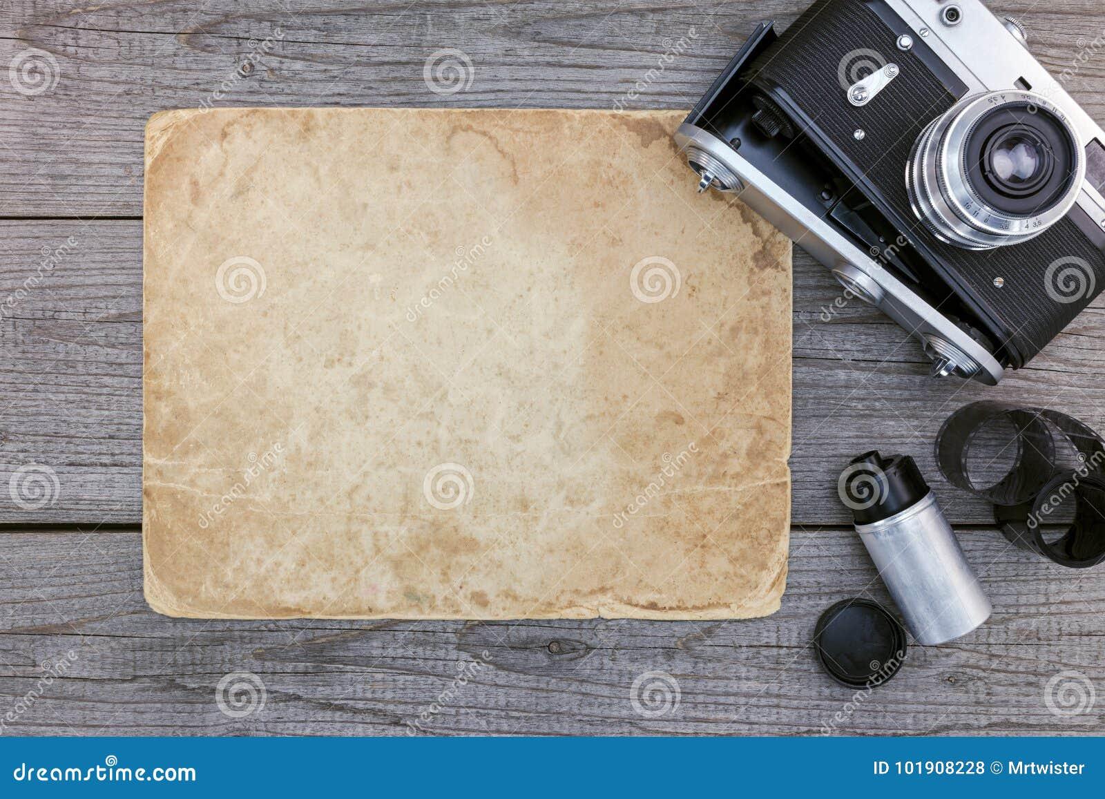Retro kamera, negatywny film i stary brown papier na szarym drewnianym t,