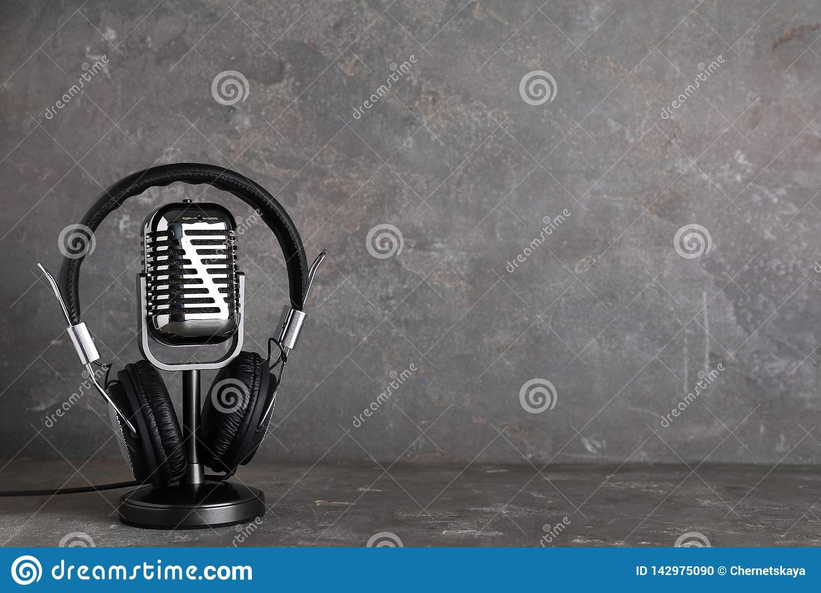 Retro microphone and headphones on table against grey background