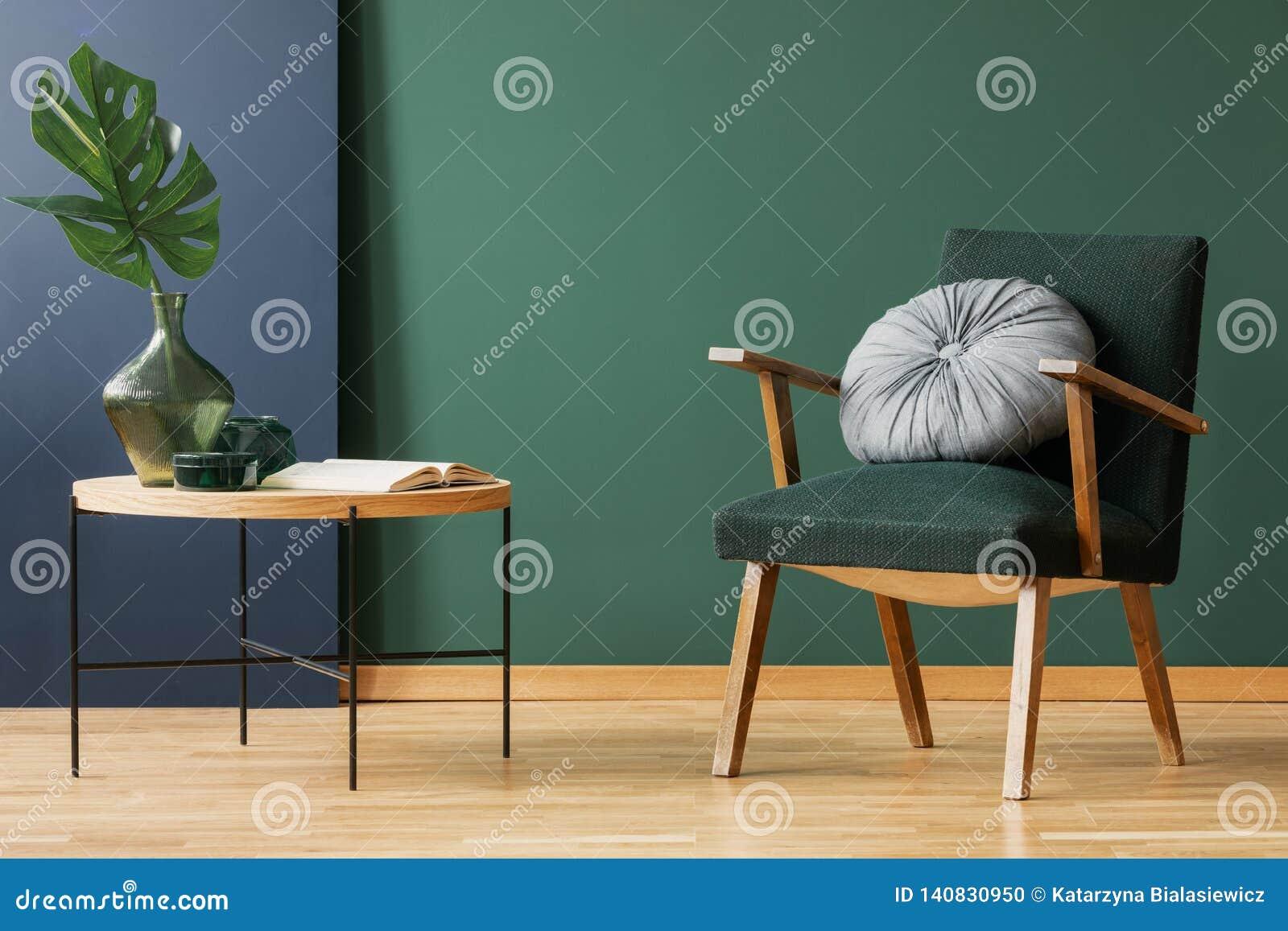 Retro poltrona verde del muschio con il giro, cuscino d argento accanto al tavolino da salotto di legno con la foglia in vaso di