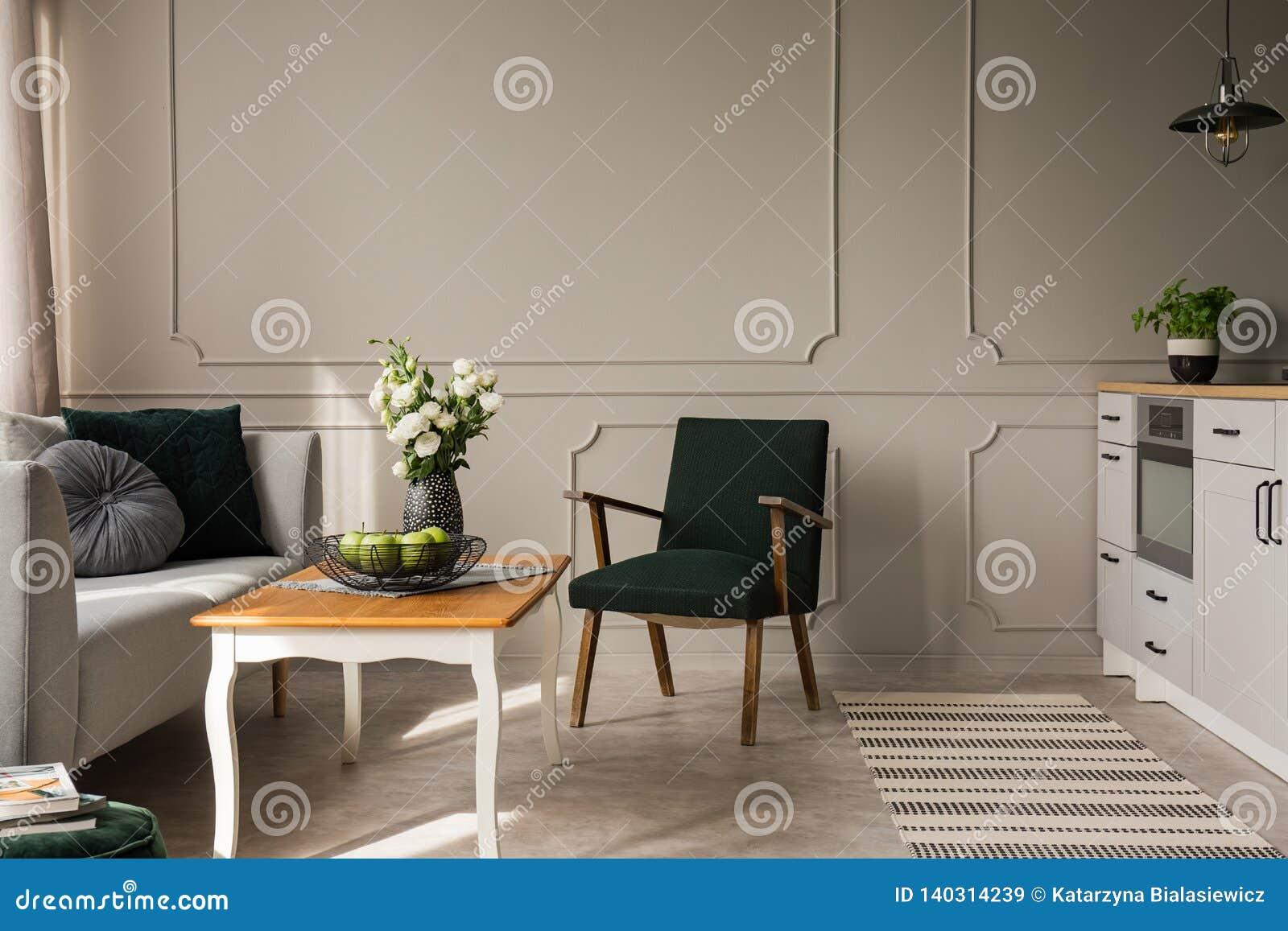 Retro poltrona verde scuro accanto al tavolino da salotto di legno con le mele e le rose in vaso nell interno del salone e della