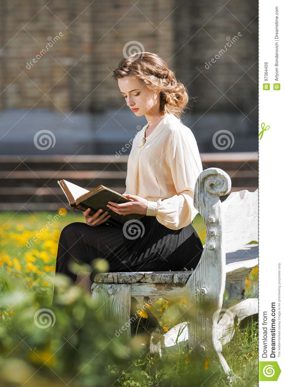 Retro portrait of a beautiful dreamy girl reading a book outdoors. Soft vintage toning.