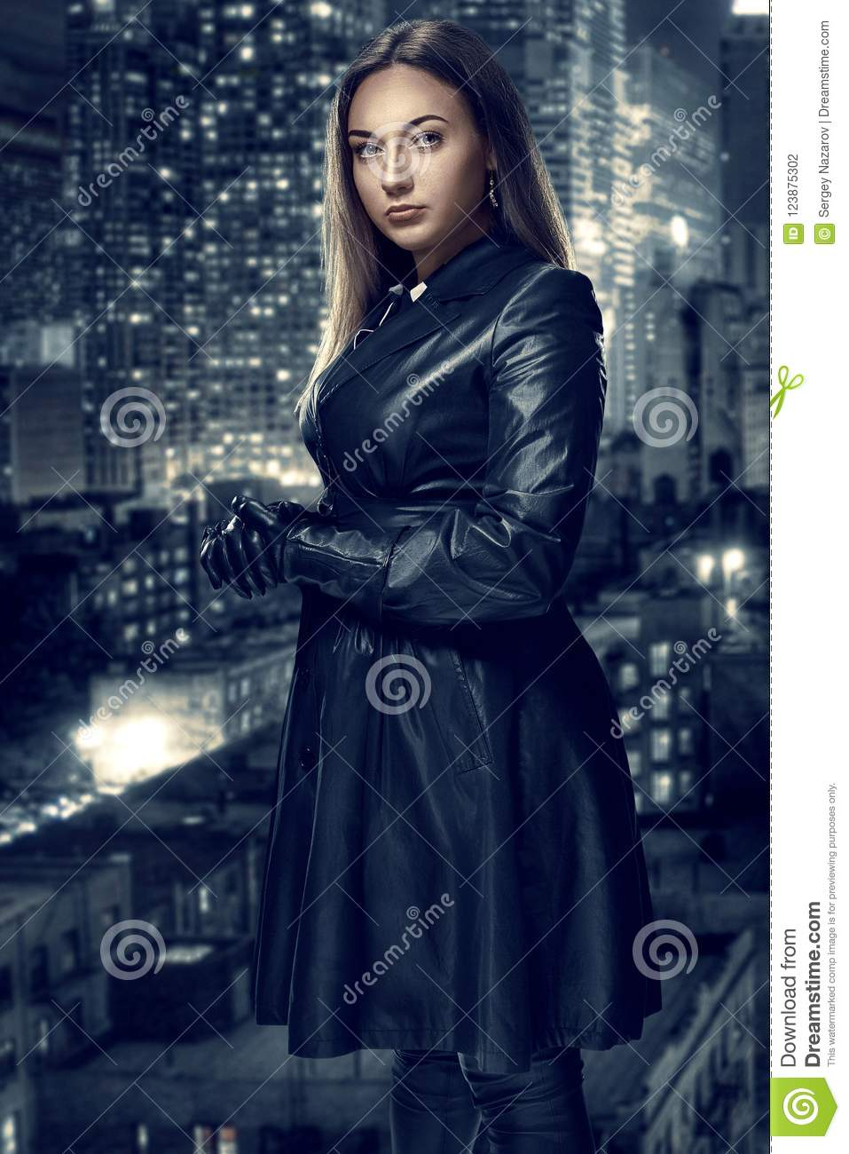 Retro portrait of inaccessible beautiful woman in black cloak stands against the background of the night city. Film noir