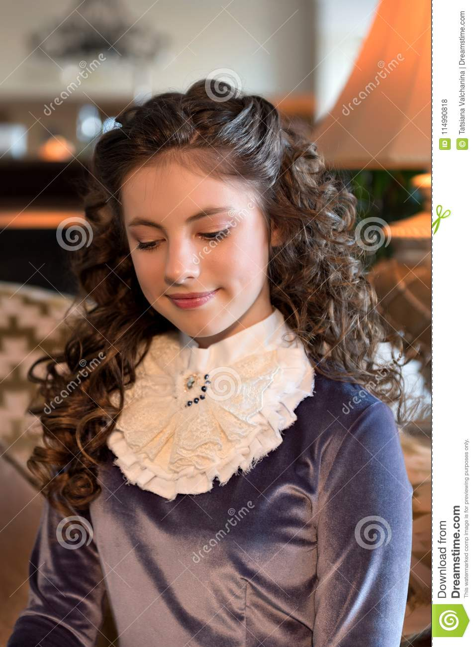 Portrait of a modest girl in an old-age interior and a vintage old-fashioned dress of the 1920s