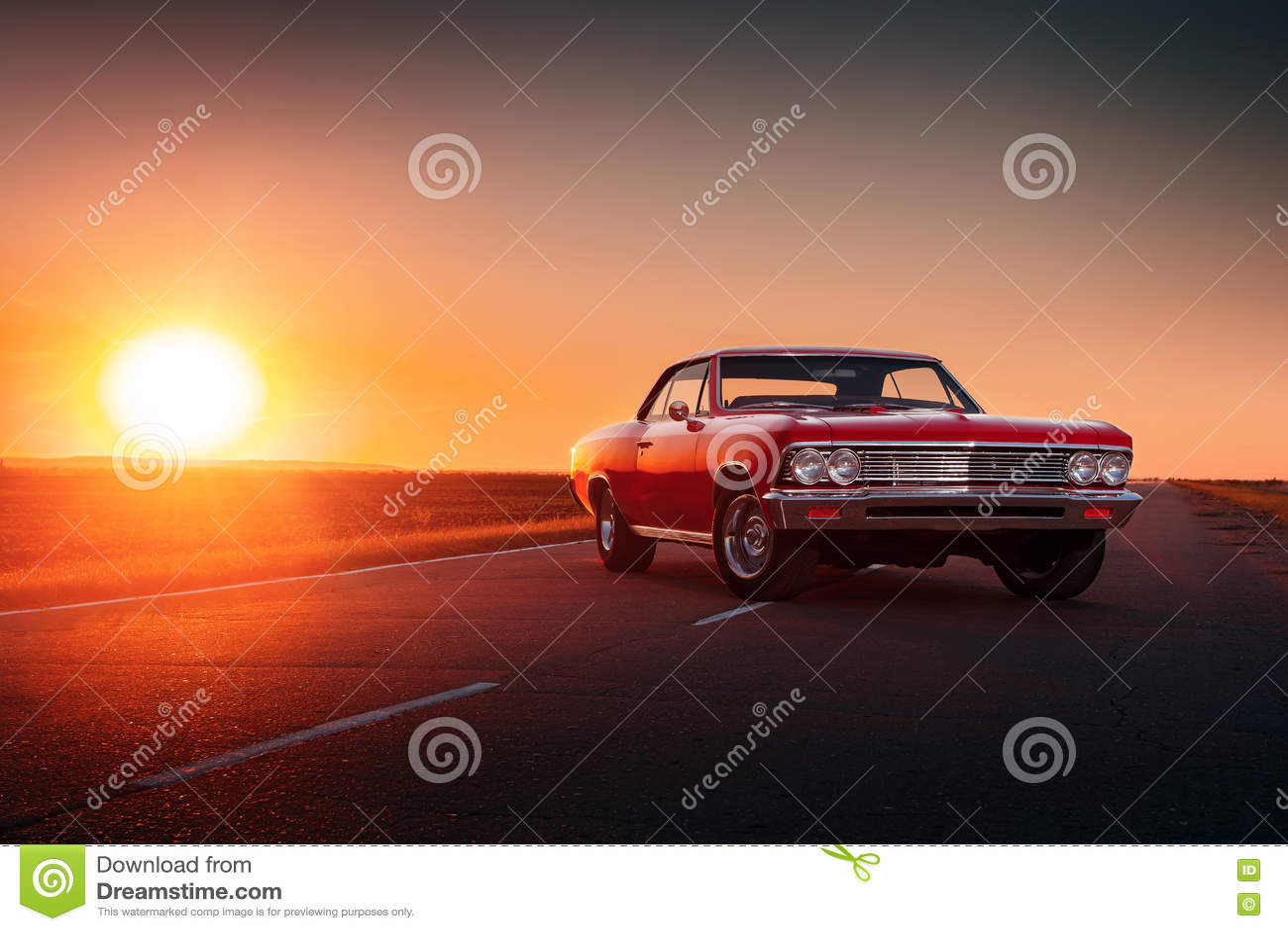 Retro red car standing on asphalt road at sunset
