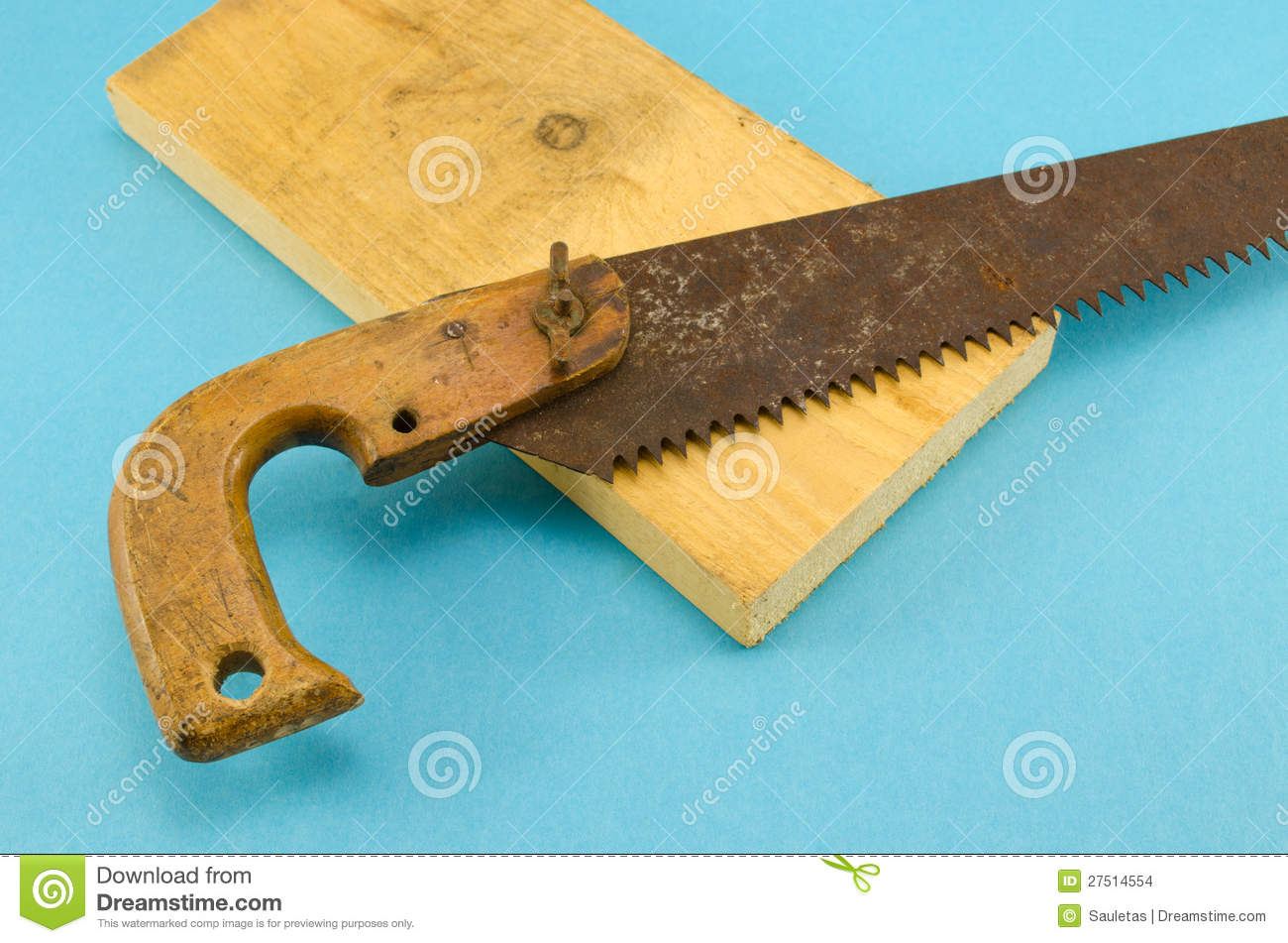 wood hand saw. retro rusty hand saw and wood board part on blue c