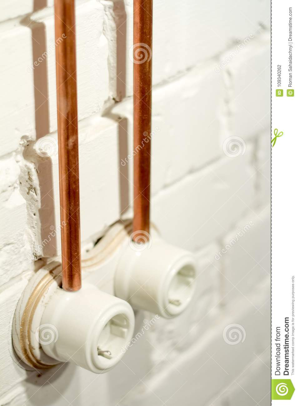 A Vintage Outlet And Electrical Wiring In Copper Tube Stock Photo An Old Retro Socket Made Of White Ceramic With Open Against The Background Brick Wall Pipes